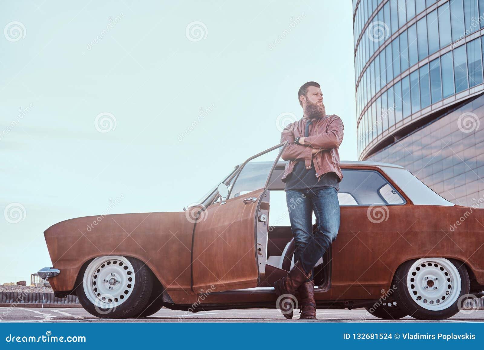Stilfull skäggig man i gammalmodig kläder som lutar på en stämd gammal retro bil med den öppna dörren i staden som nära parkerar