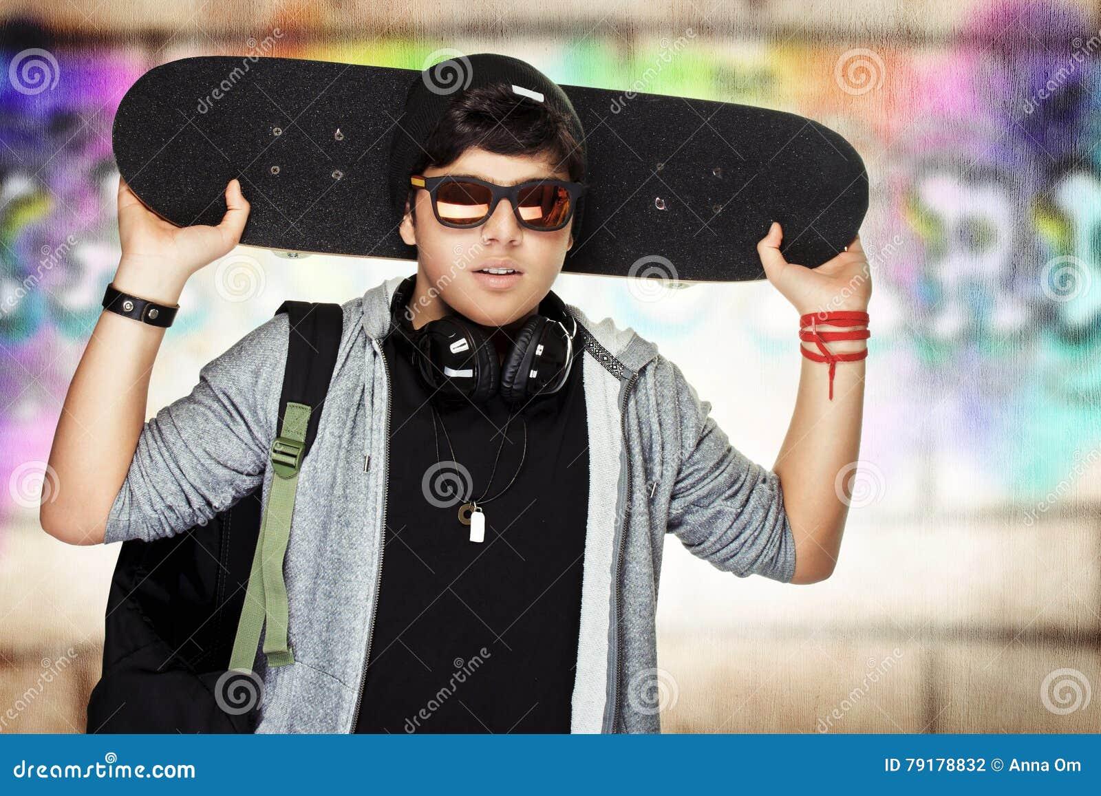 Stilfull tonårig pojke med skateboarden