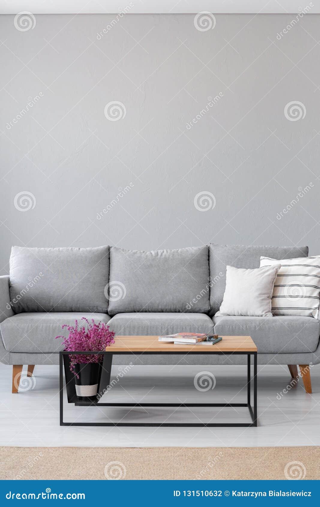 Stilfull träkaffetabell med tidskrifter och ljung bredvid den gråa soffan med vita kuddar