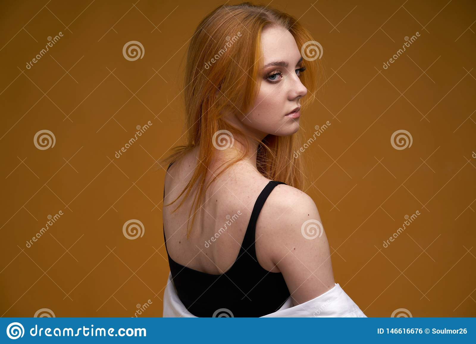 Stilfull ung flicka med lockigt h?r och att le cutely som poserar, p? gul bakgrund