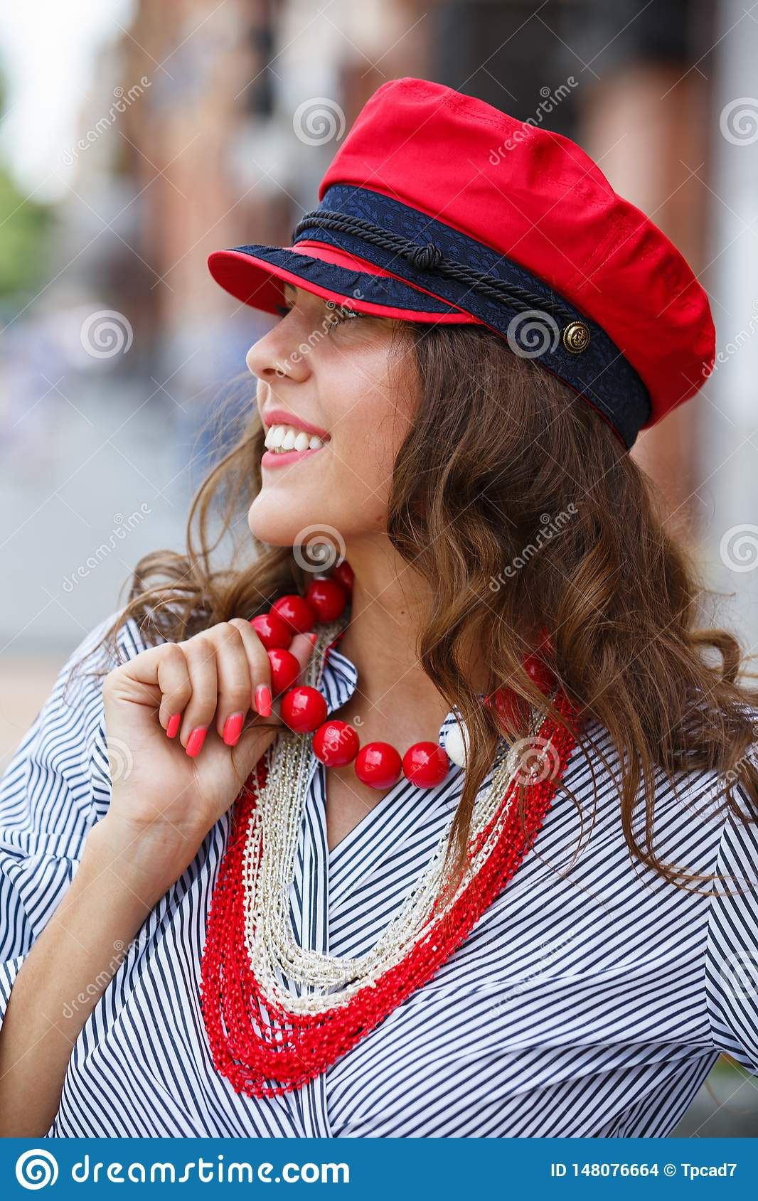 Stilfulla den iklädda brunettflickan en randig blus, röda pärlor och ett rött lock poserar i stadsgatan på en solig dag