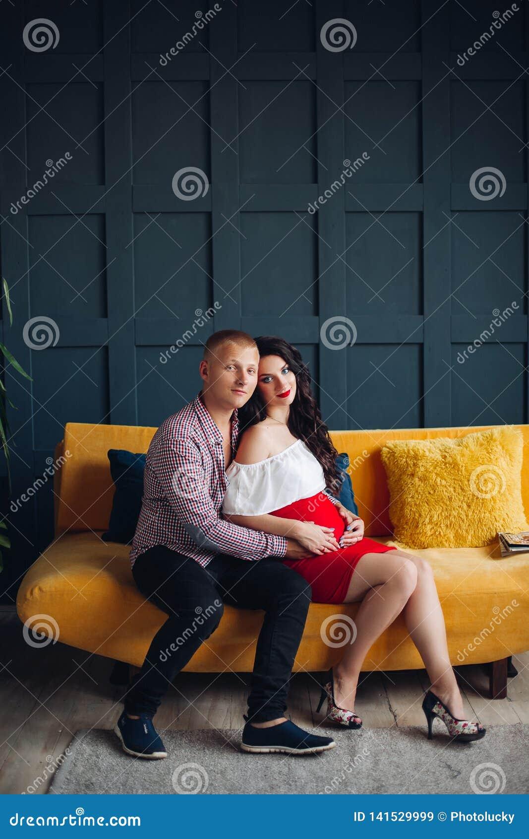 Stilfulla par som sitter på den gula soffan och ser kameran