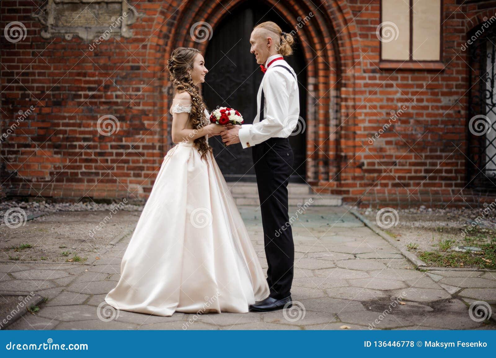 Stilfullt gift paranseende och le i bakgrunden av den gamla byggande bågen