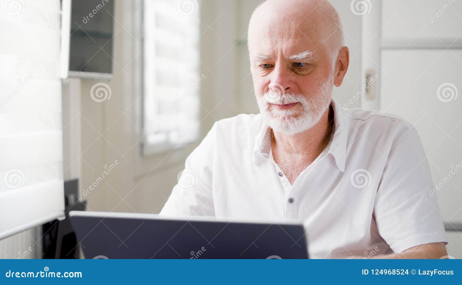 Stilig äldre hög man som hemma arbetar på bärbar datordatoren Fjärrkontrollfrilansarbete på avgång