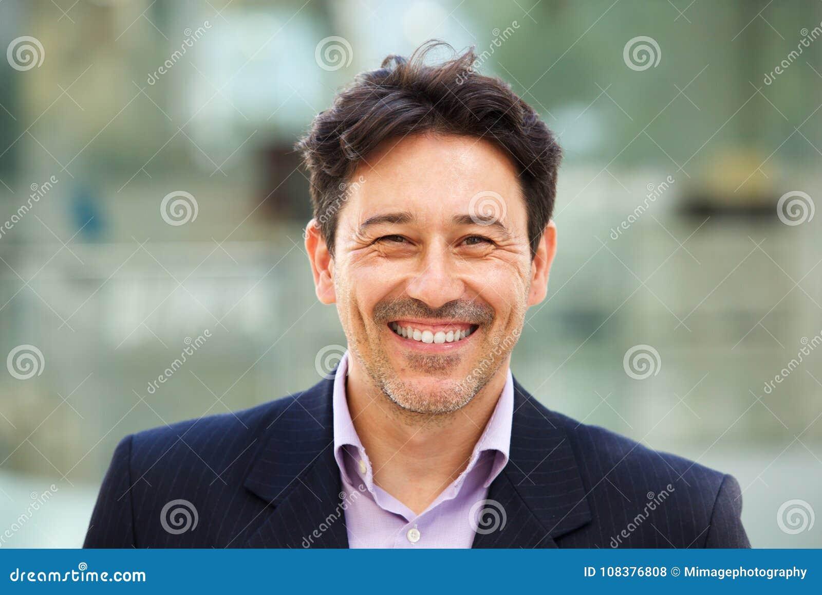 Stilig äldre man i dräkt med stort leende på hans framsida