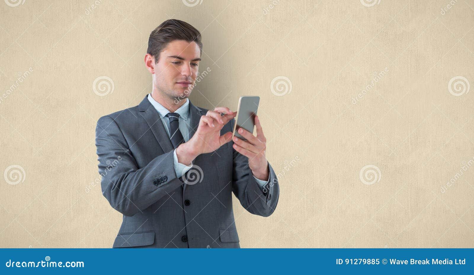 Stilig affärsman som använder den smarta telefonen över beige bakgrund