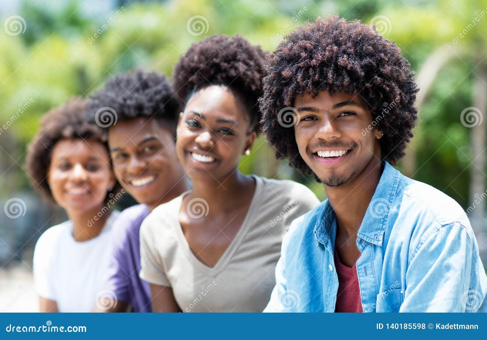 Stilig afrikansk amerikanman med gruppen av unga vuxna människor i linje