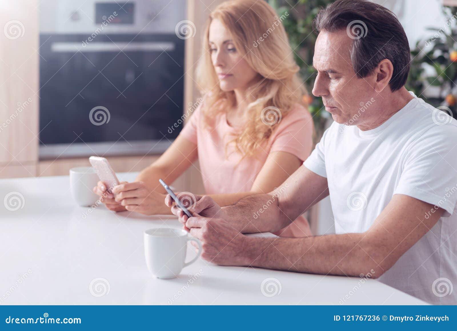 Stilig allvarlig man som fokuseras på hans telefon