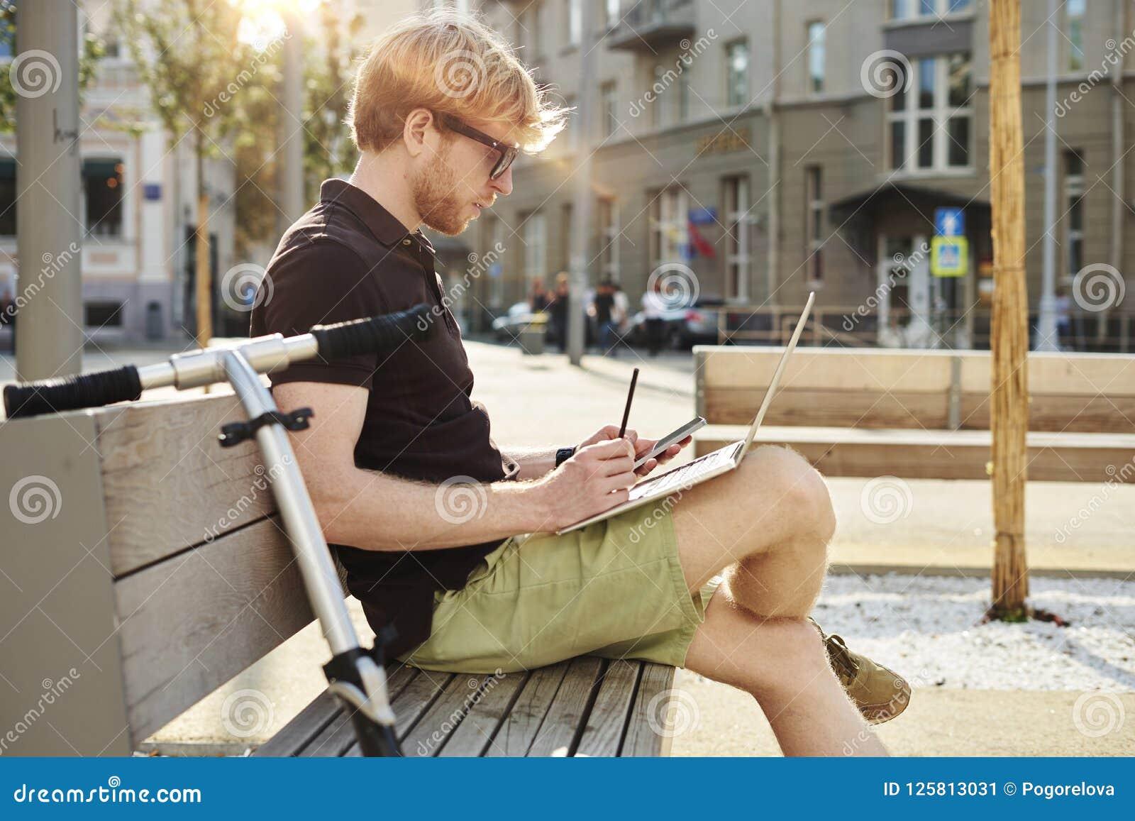 Stilig caucasian man som använder att sitta för bärbar dator som är utomhus- i en parkera Sommarsolskendag Begrepp av ungt arbeta