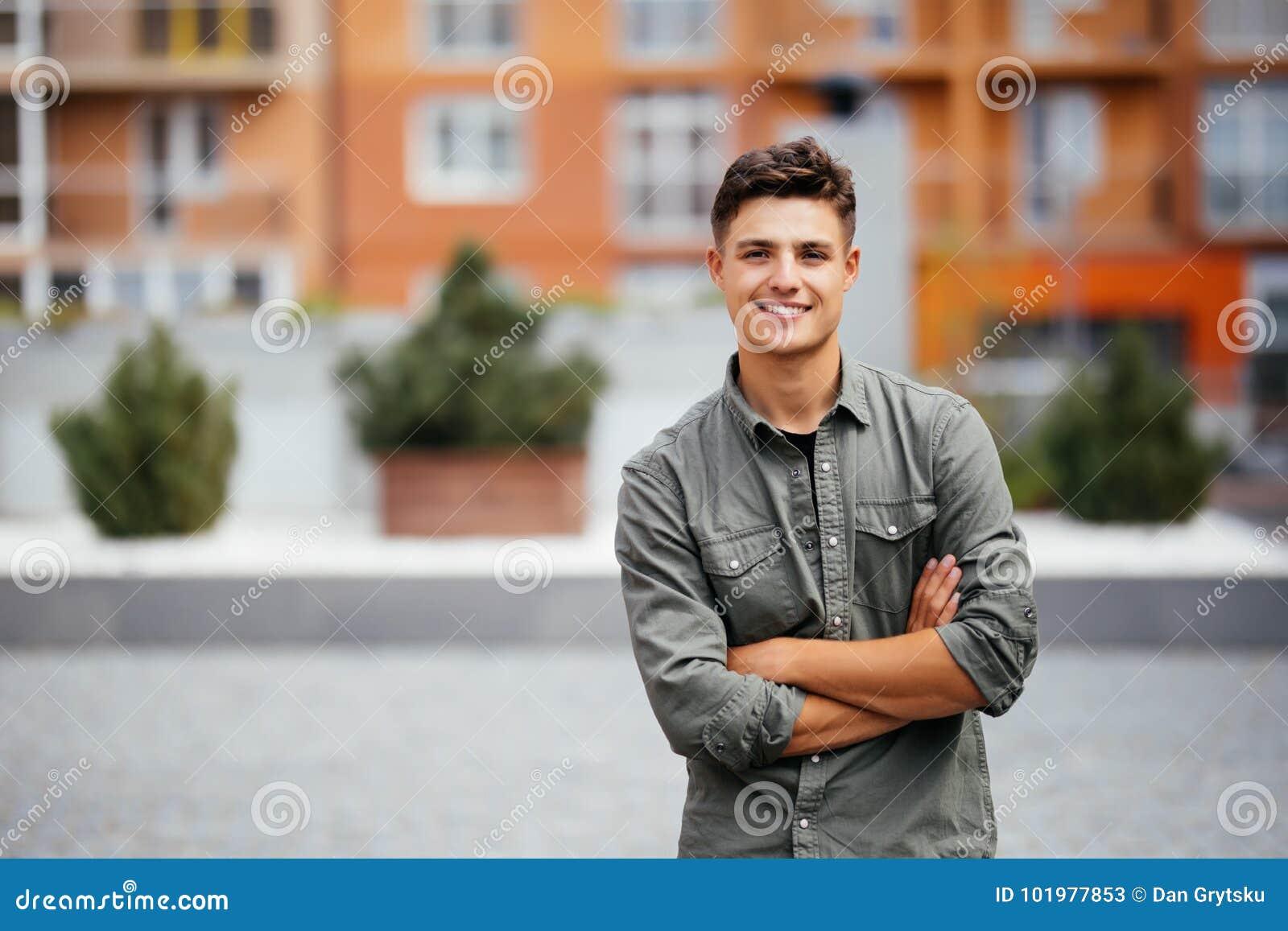 Stilig le stående för ung man Gladlynt man som ser kameran