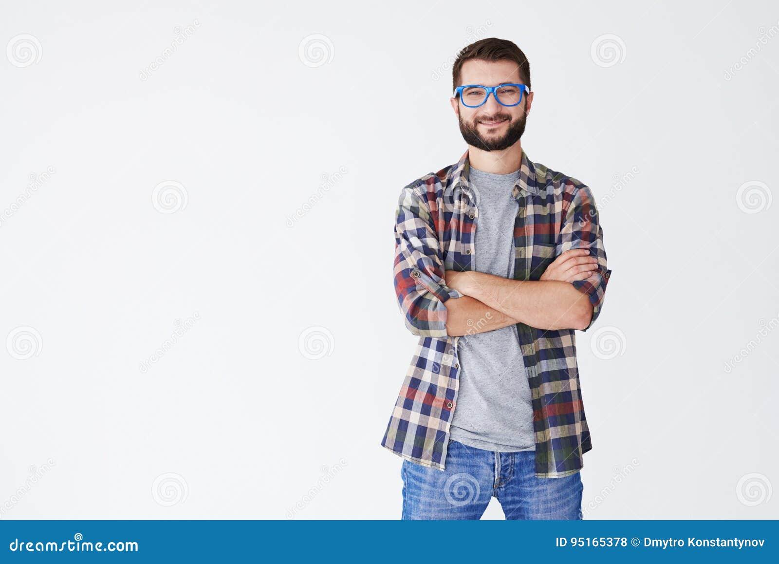 Stilig man i blåa exponeringsglas som står med vikta armar