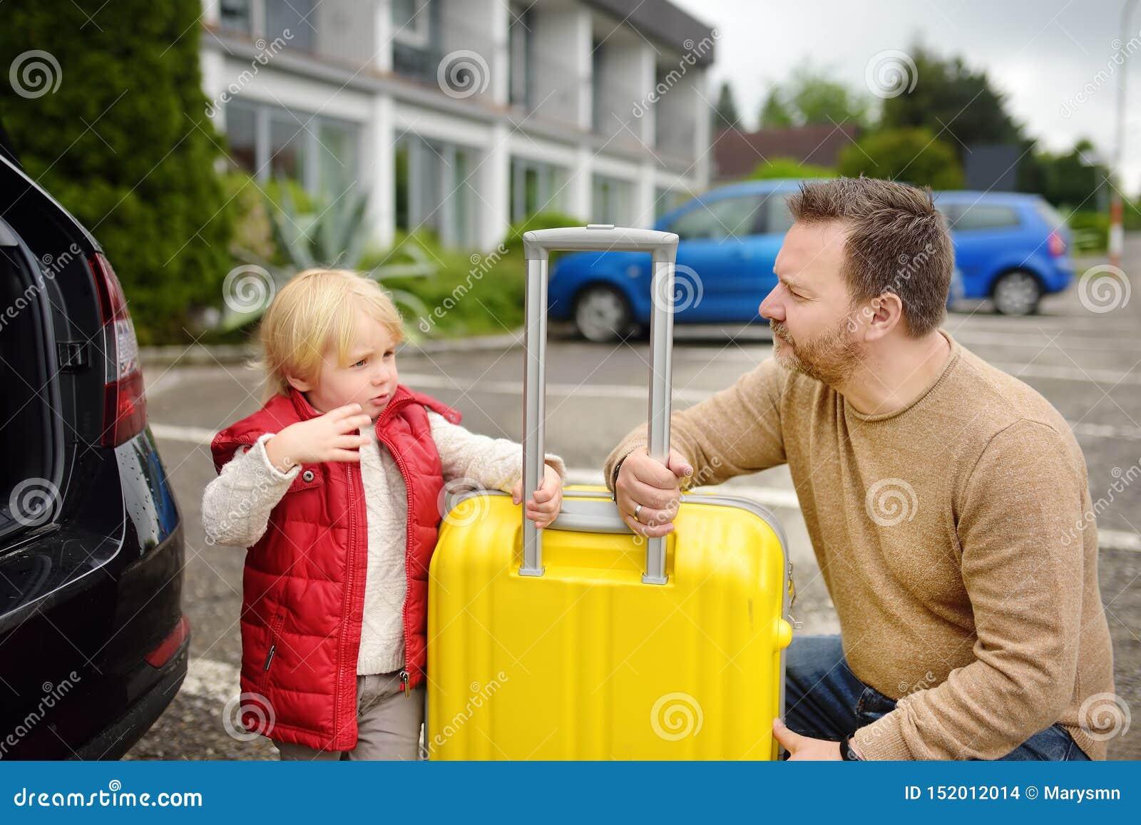 Stilig man och hans semestrar f?r liten son som g?ende laddar deras resv?ska i bilstam Biltur i bygden