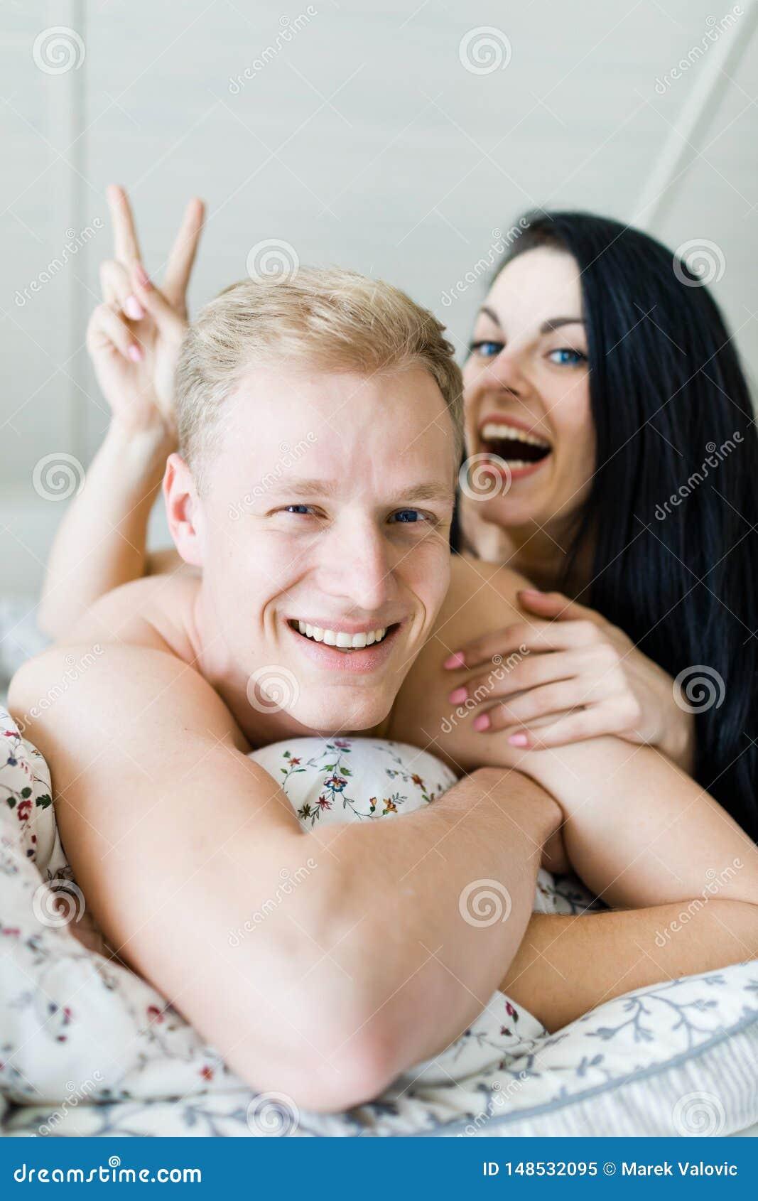 Stilig man och trevlig kvinna som poserar i säng - seger