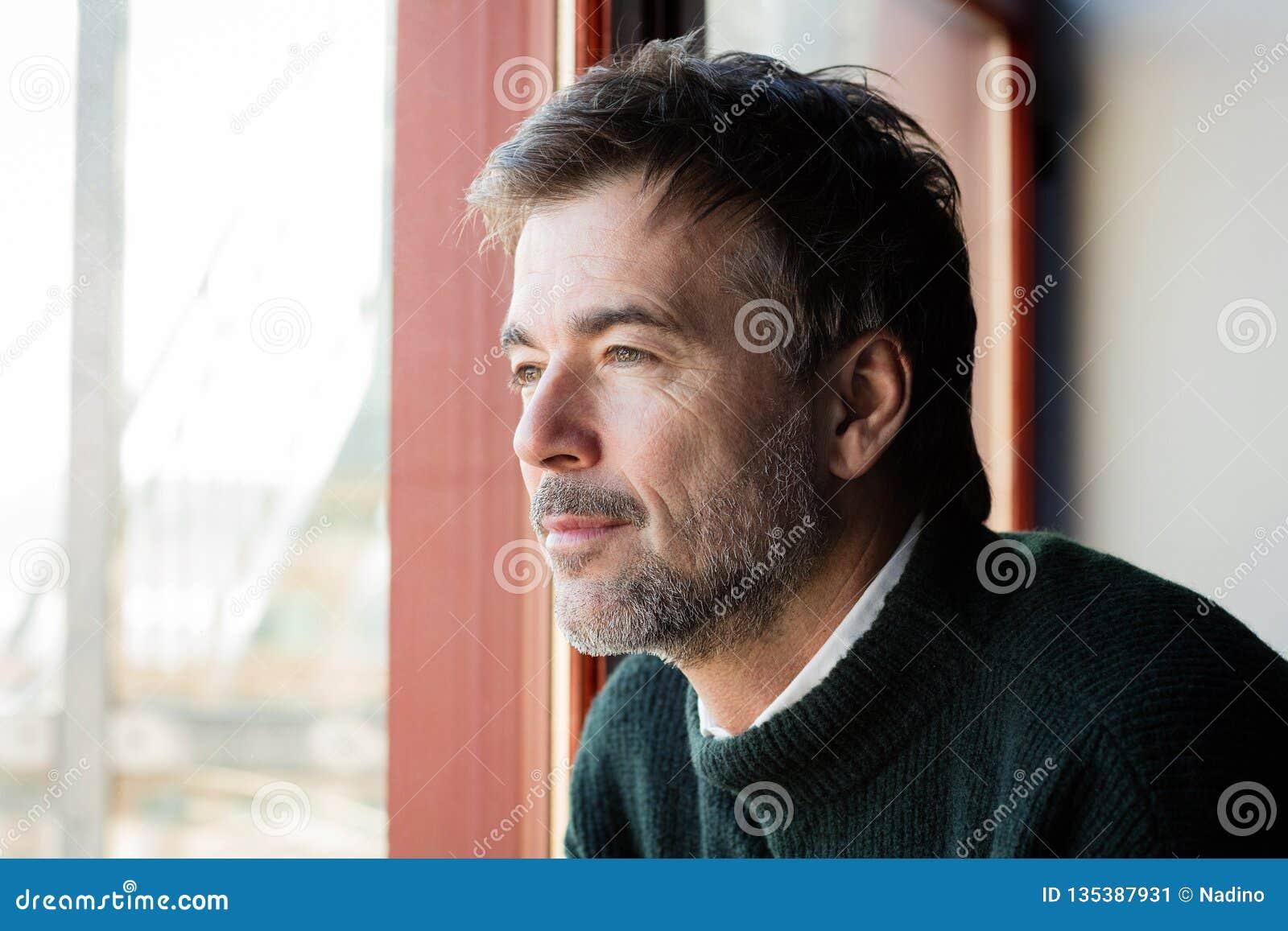 Stilig man som förloras i tanke Honom allvarlig ` s På fönstret