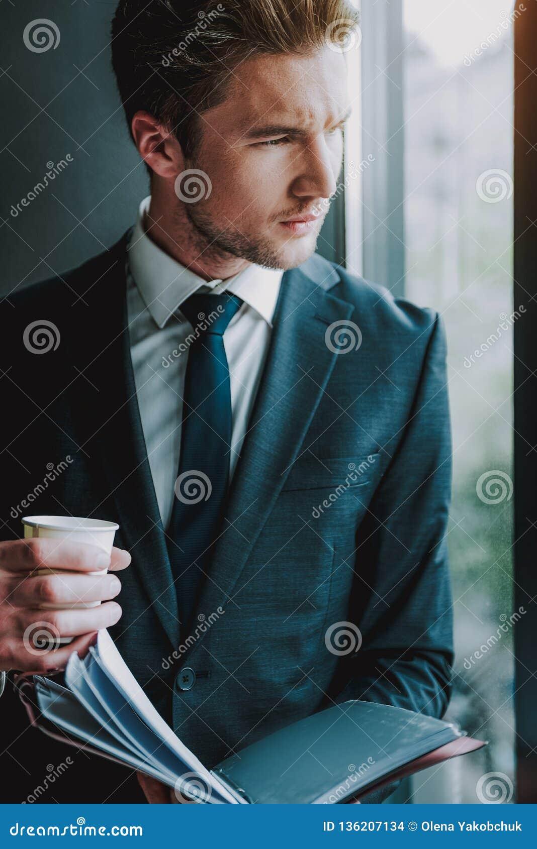 Stilig man som ser ut ur fönstret och rynka pannan