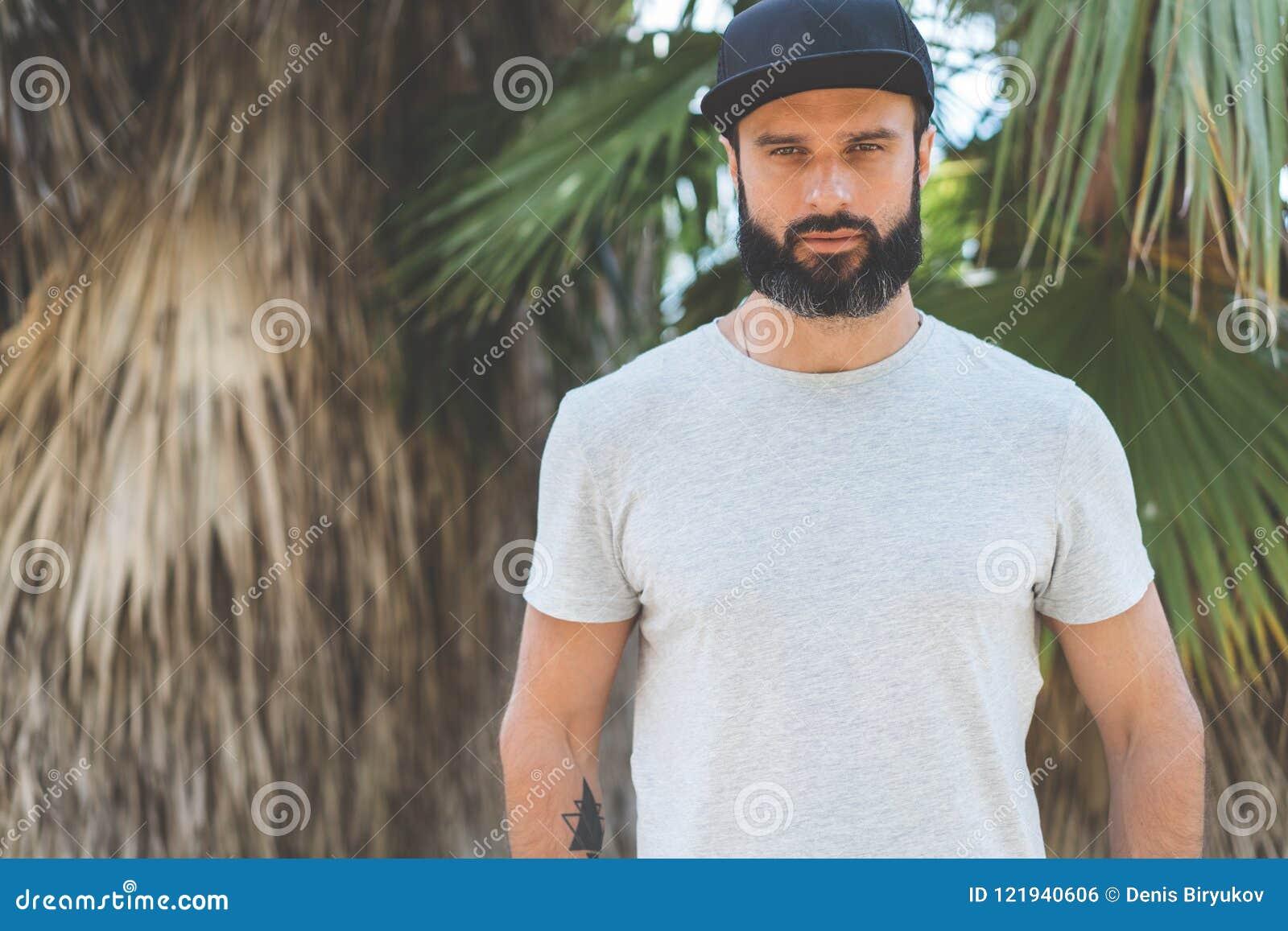 Stilig manlig modell för Hipster med t-skjortan för grå färger för skägg den bärande tomma och ett svart snapbacklock med utrymme