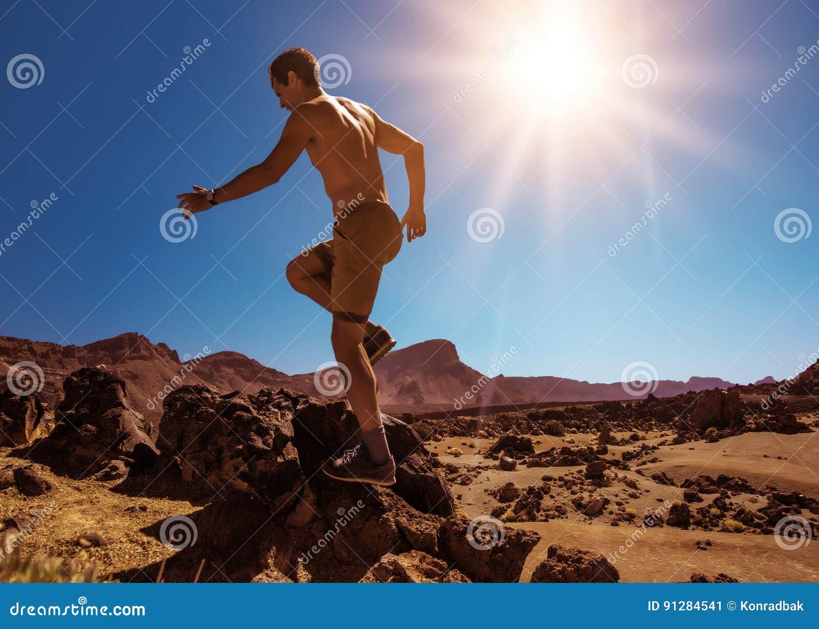 Stilig muskulös manspring på öknen
