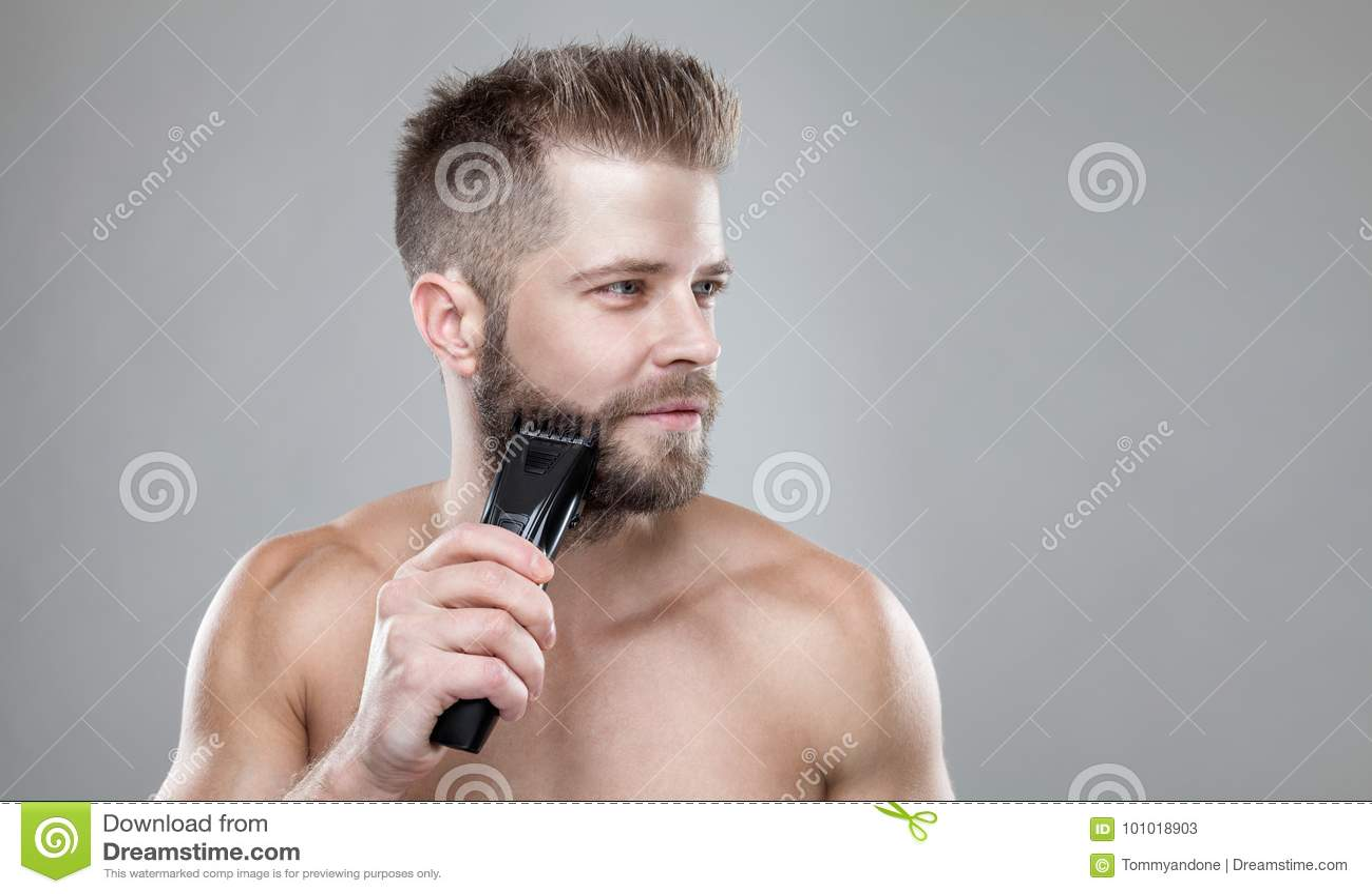 Stilig skäggig man som klipper hans skägg med en beskärare