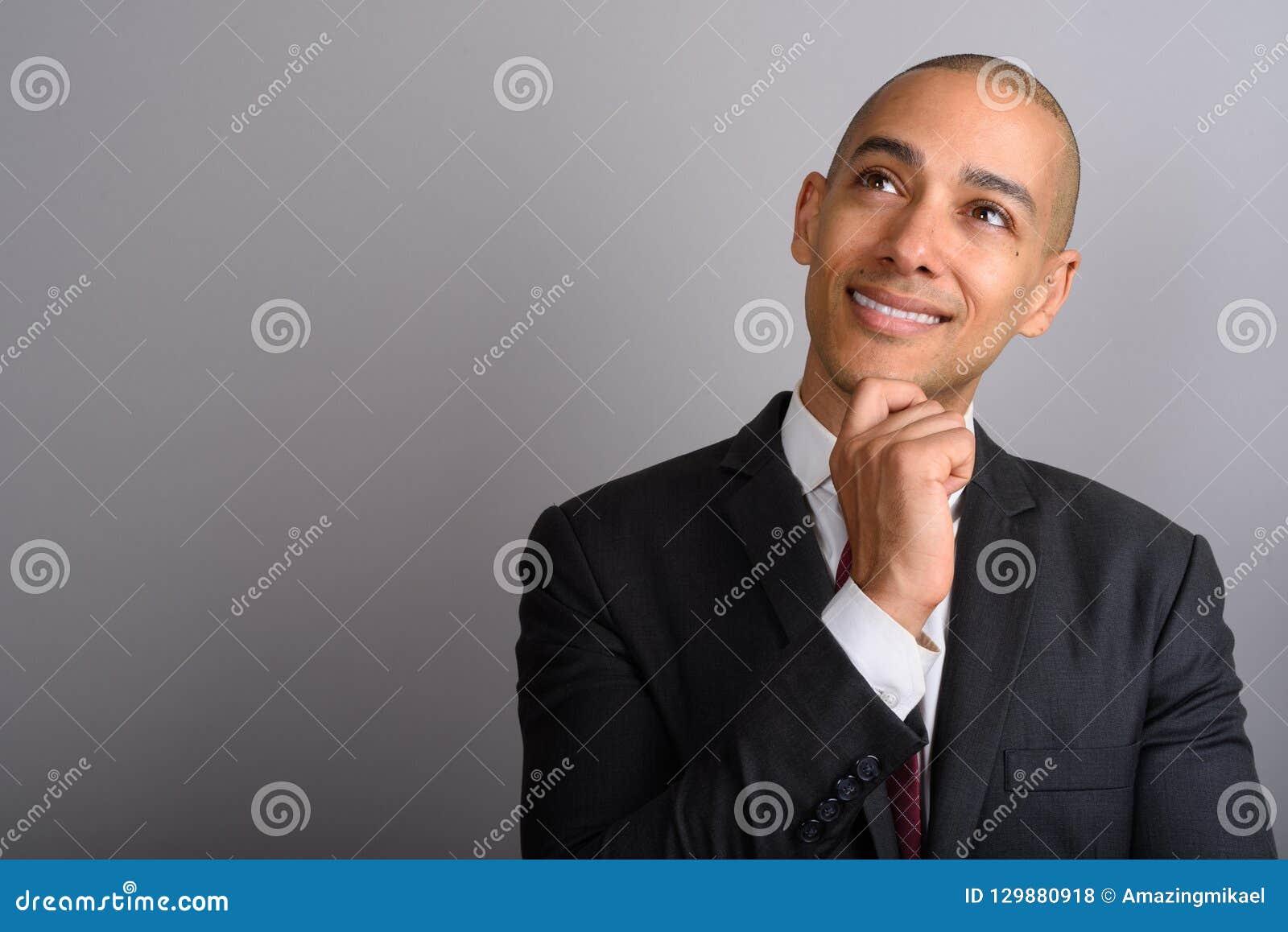 Stilig skallig affärsman som tänker och ser upp