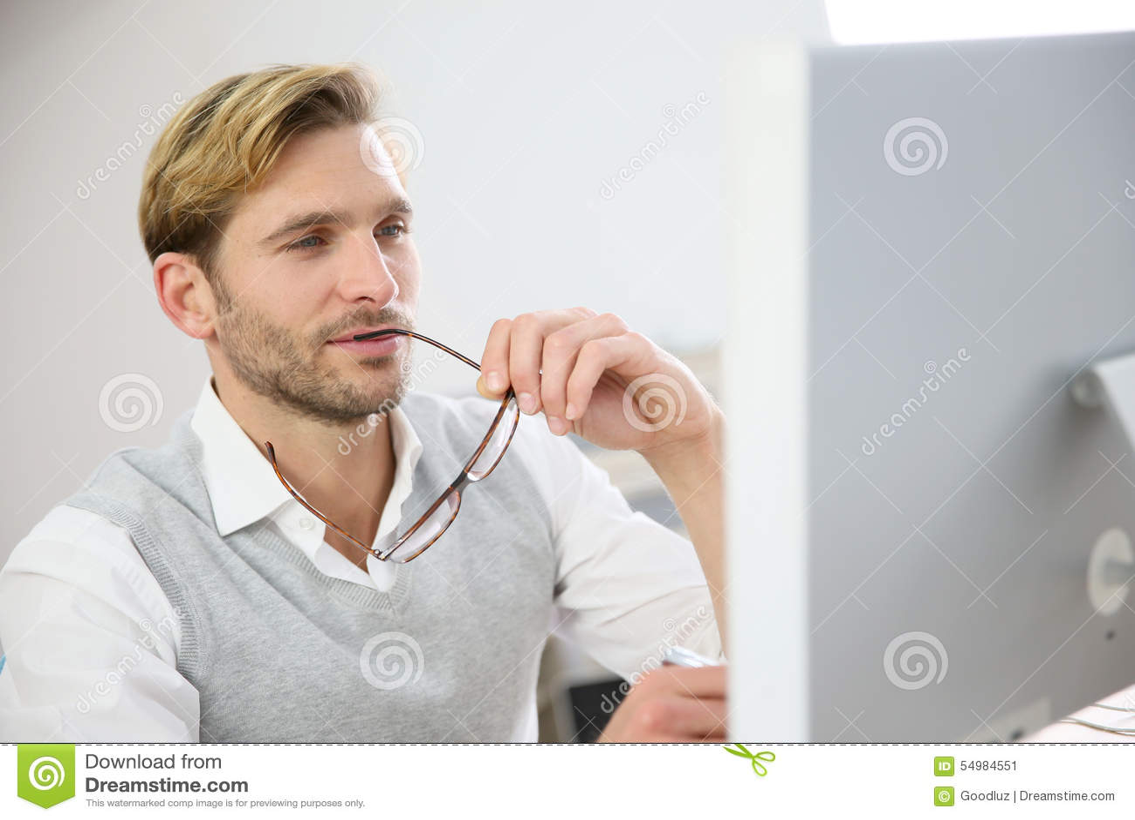 Stilig ung affärsman som arbetar på datoren