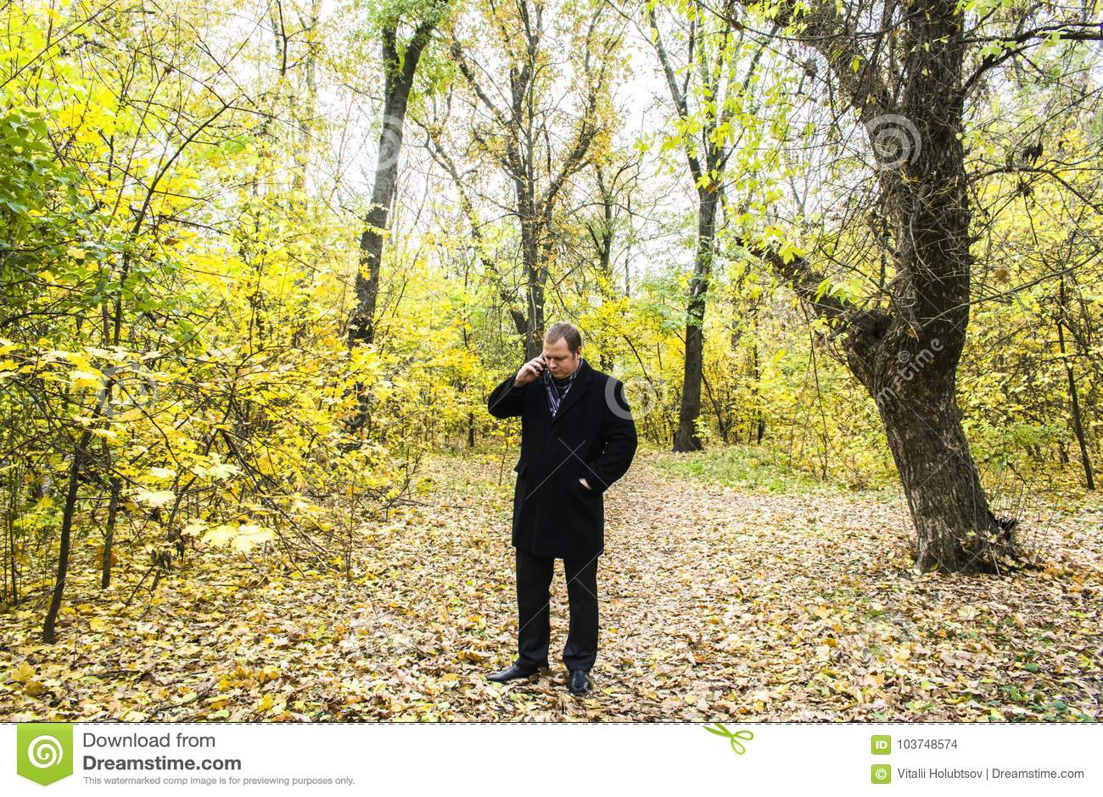 Stilig ung man med en smartphone på gatan som talar i parkera
