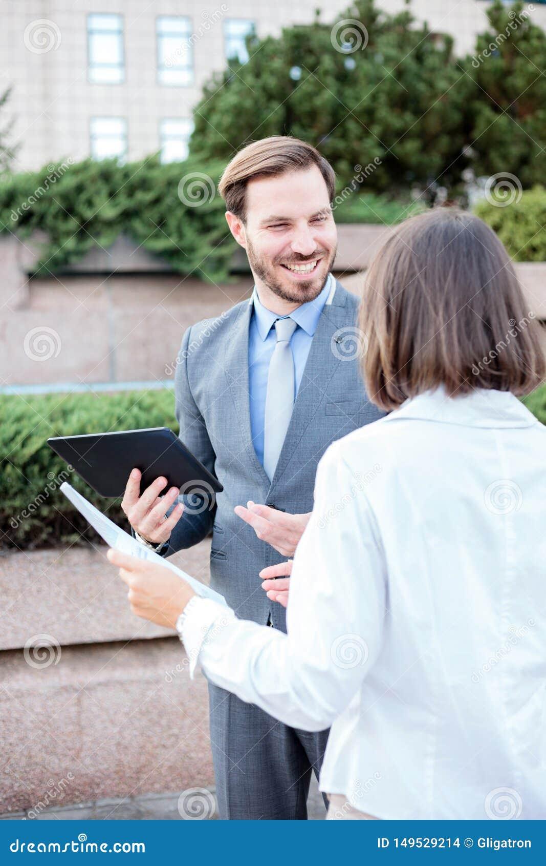 Stilig ung man och kvinnligt affärsfolk som framme talar av en kontorsbyggnad, har ett möte och diskuterar
