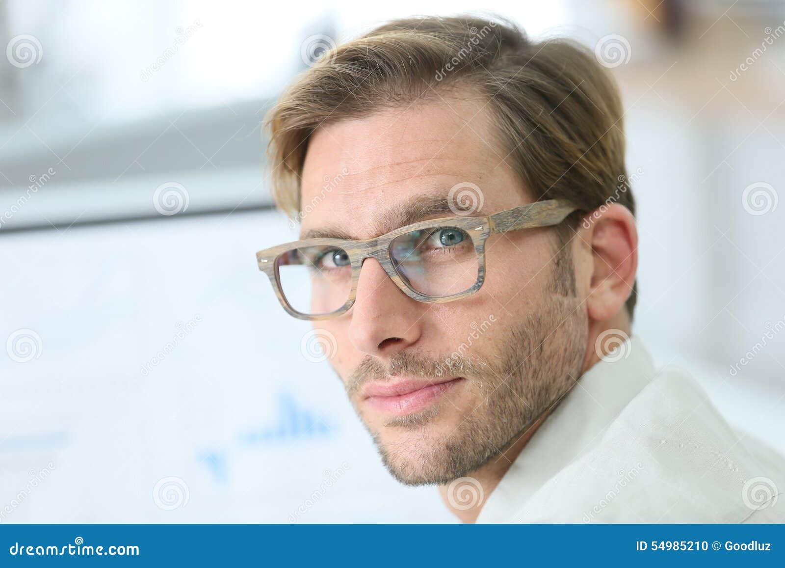 Stilig ung man som bär moderiktigt glasögon