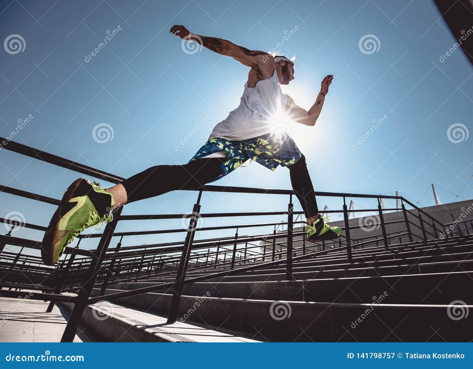 Stilig ung muskulös man i modern sportklädkörning upp trappan som är utomhus- på den ljusa soliga dagen Brett vinkelfoto av