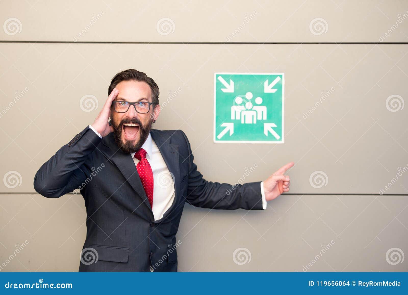 Stilig yrkesmässig ledare som pekar extremt till möte av punkttecknet Chef i dräkt och rött band som kallar för möte