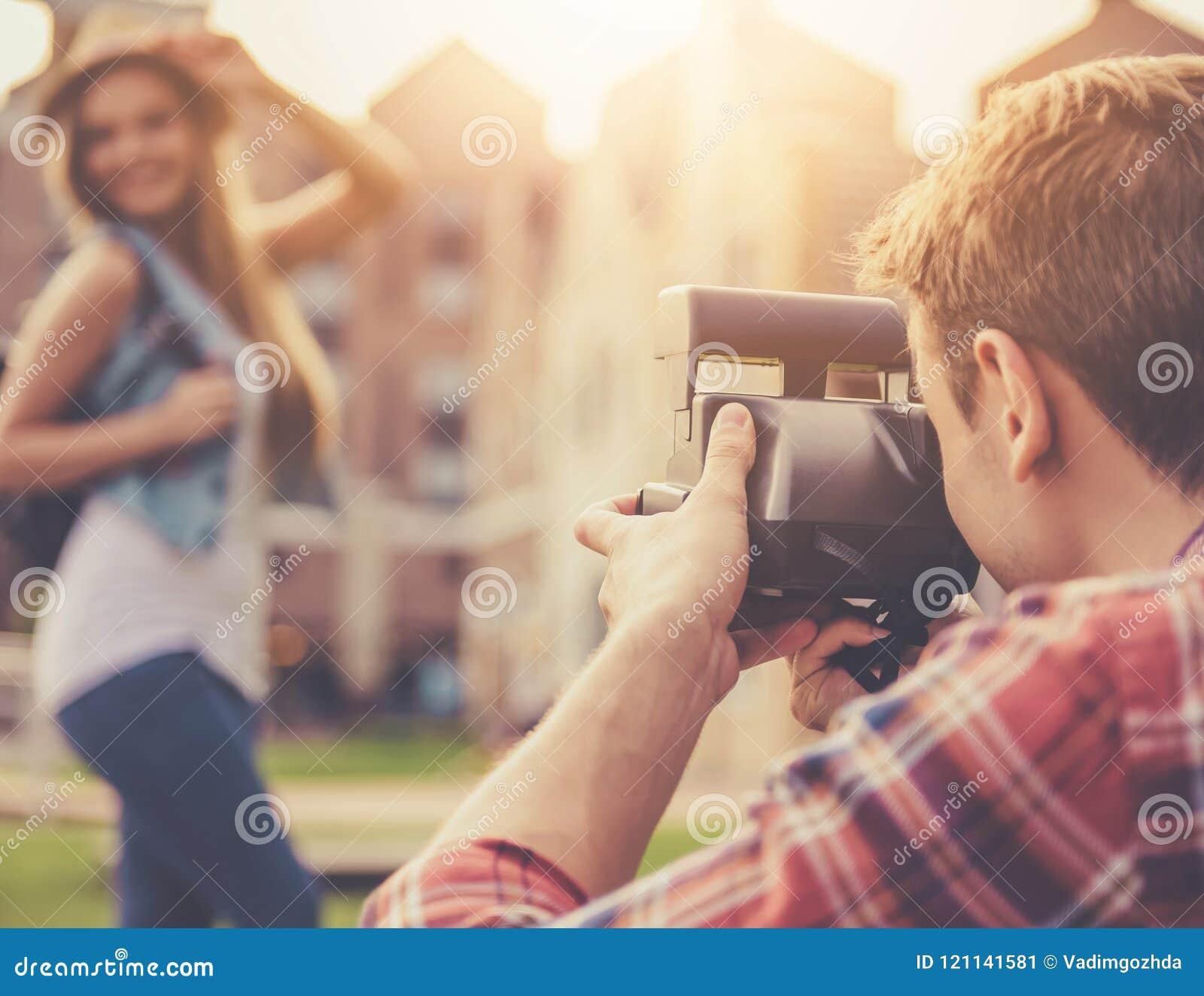 Stiliga Guy Takes Pictures av den attraktiva flickan