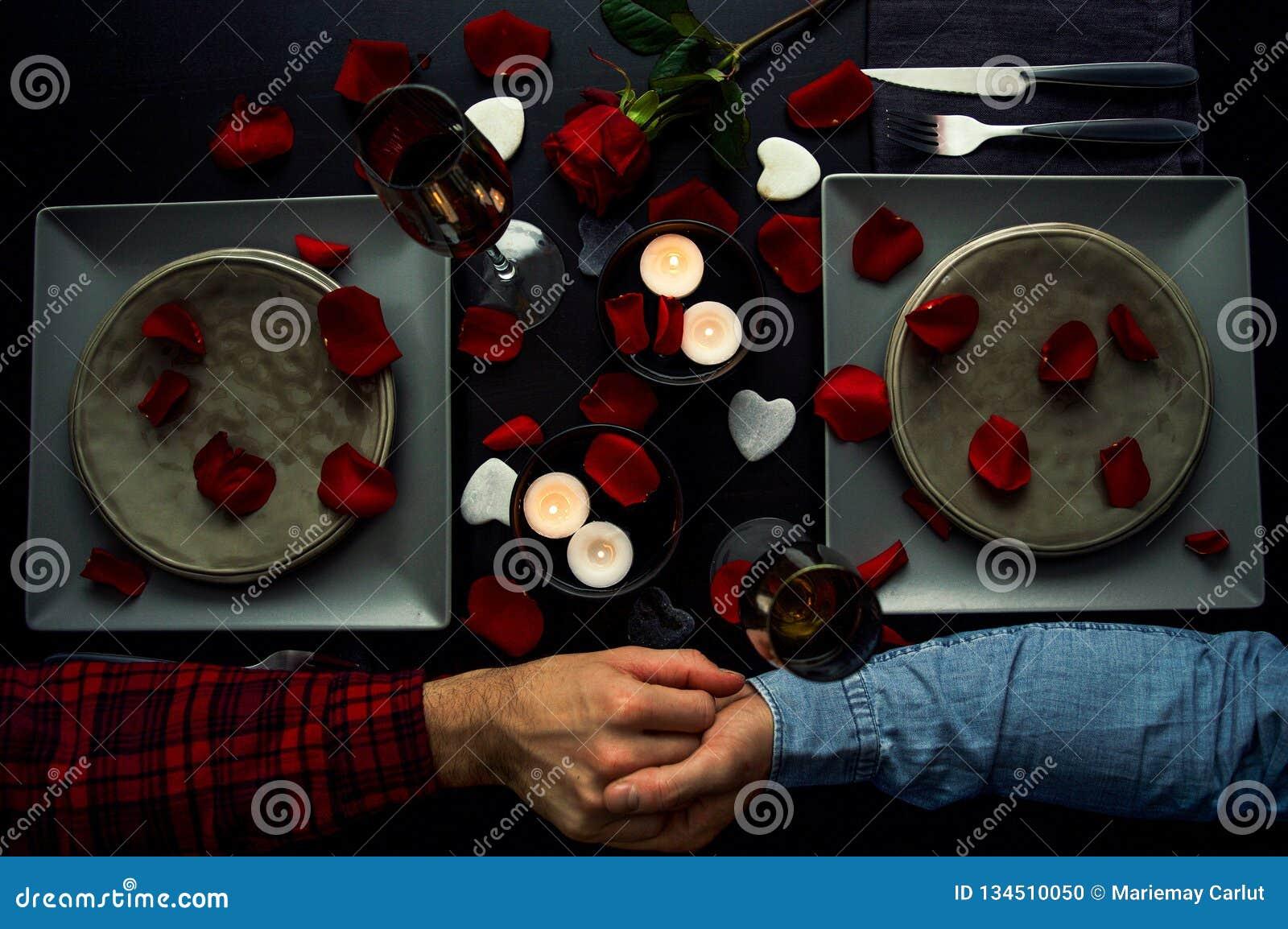 Stiliga unga par som har den romantiska matställen som rymmer händer Top beskådar Stearinljus, blommor och vin