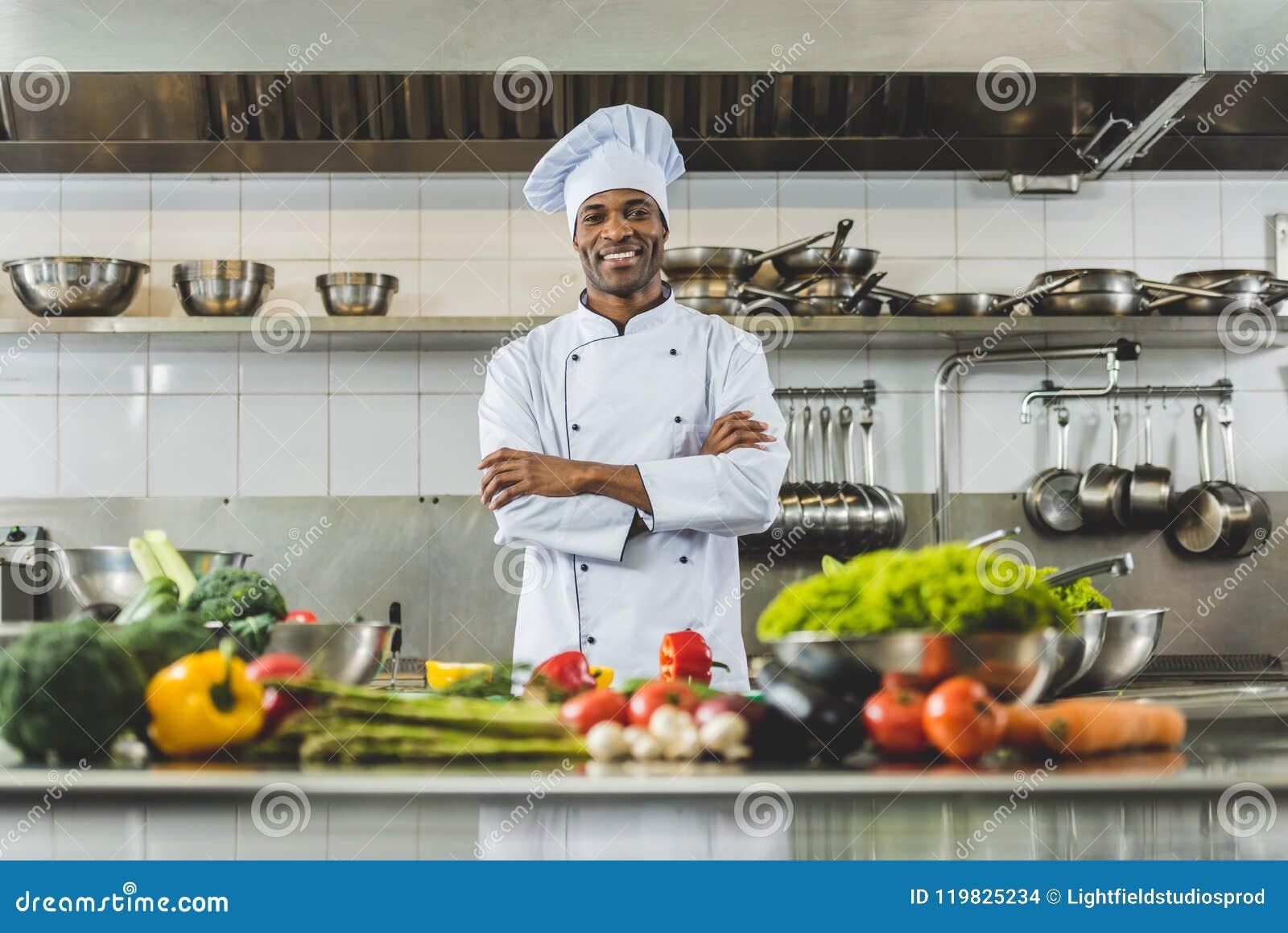 Stiligt afrikansk amerikankockanseende på restaurangkök med korsade armar och att se
