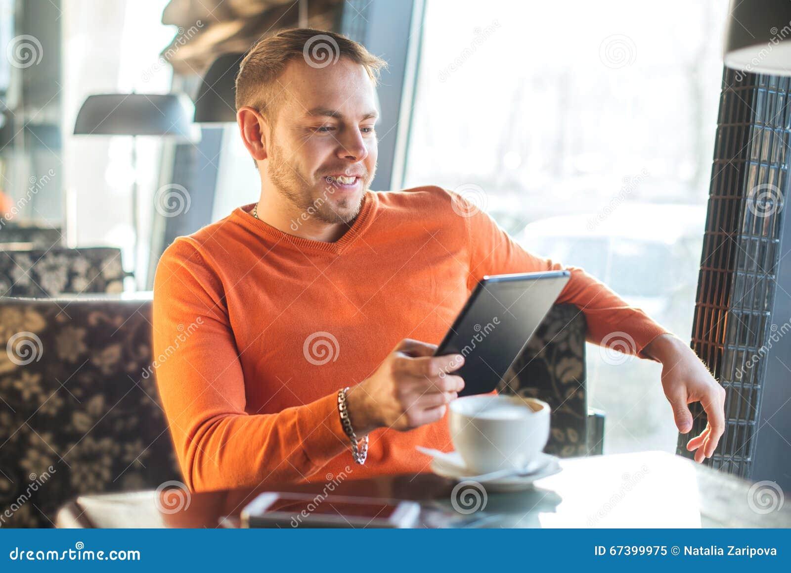 Stiligt arbete för ung man som ser in i minnestavlan, medan tycka om kaffe i kafé