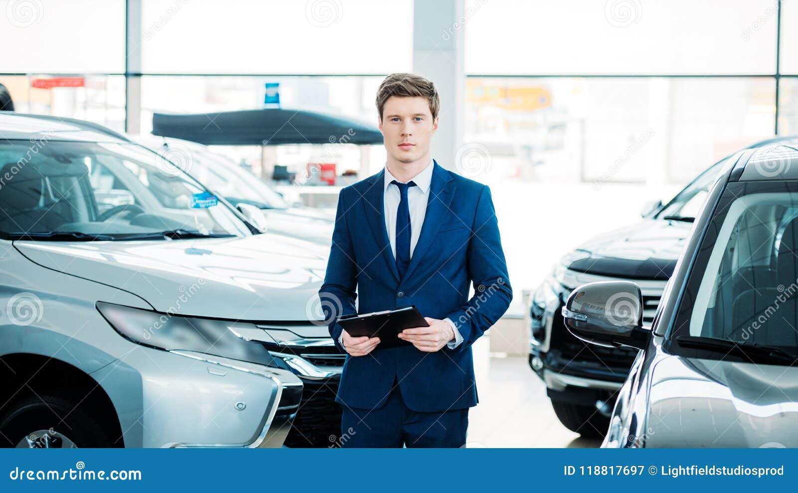 Stiligt chefanseende mellan bilar i bilvisningslokal och att se