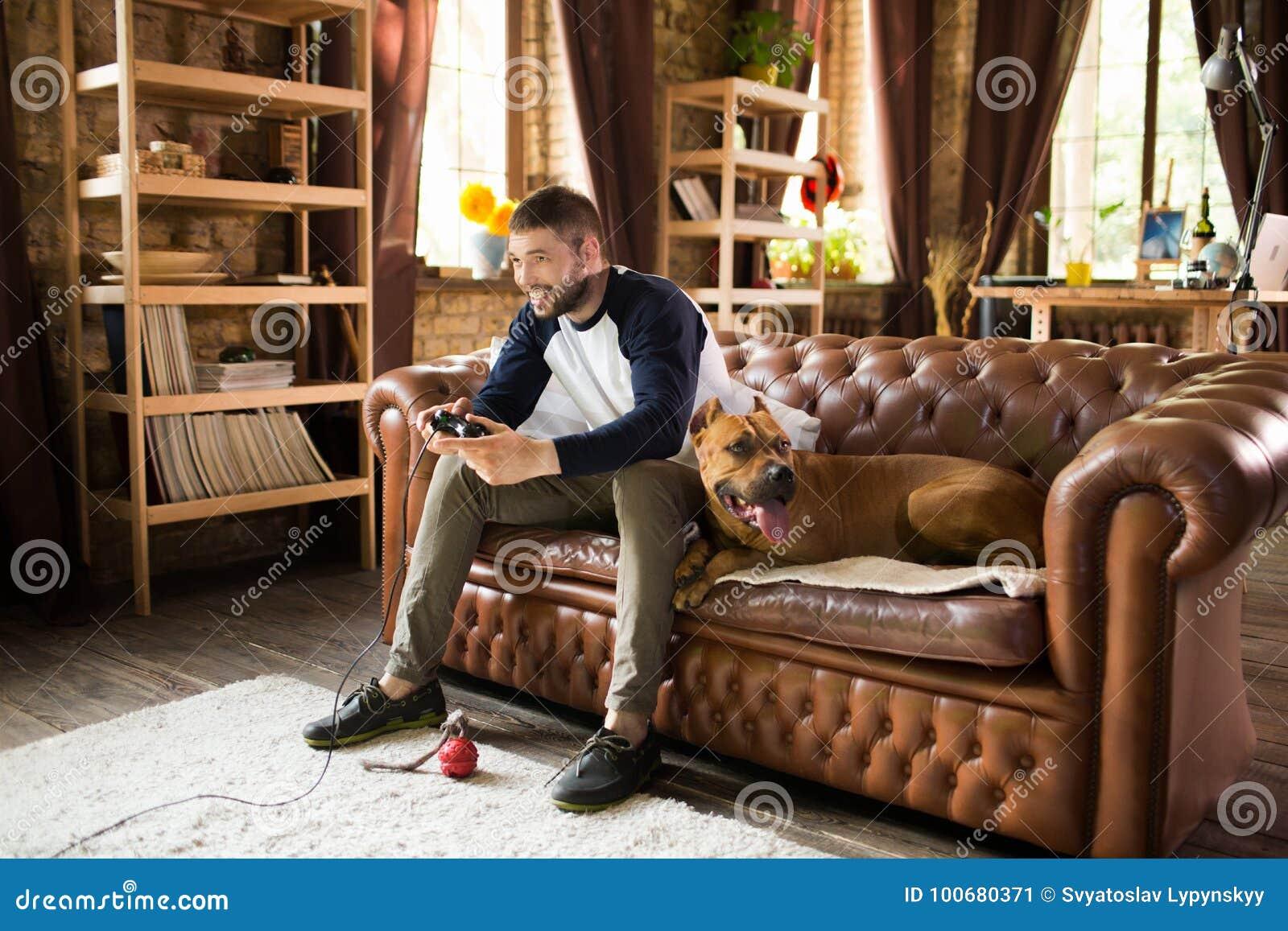 Stiligt grabbsammanträde på soffan med hans hund som spelar videospelet