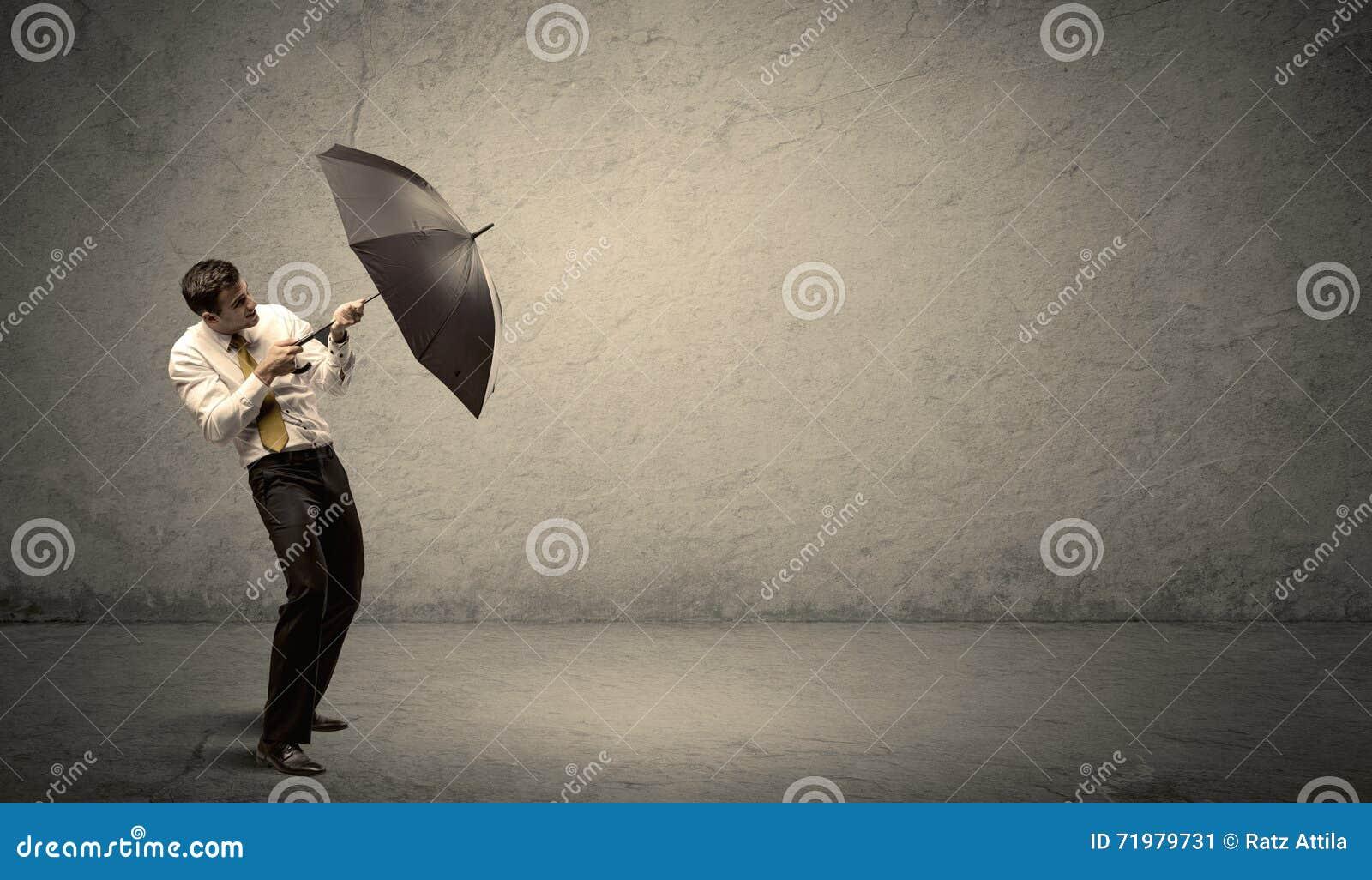 Stiligt hållande paraply för affärsman med kopieringsutrymmebackgroun