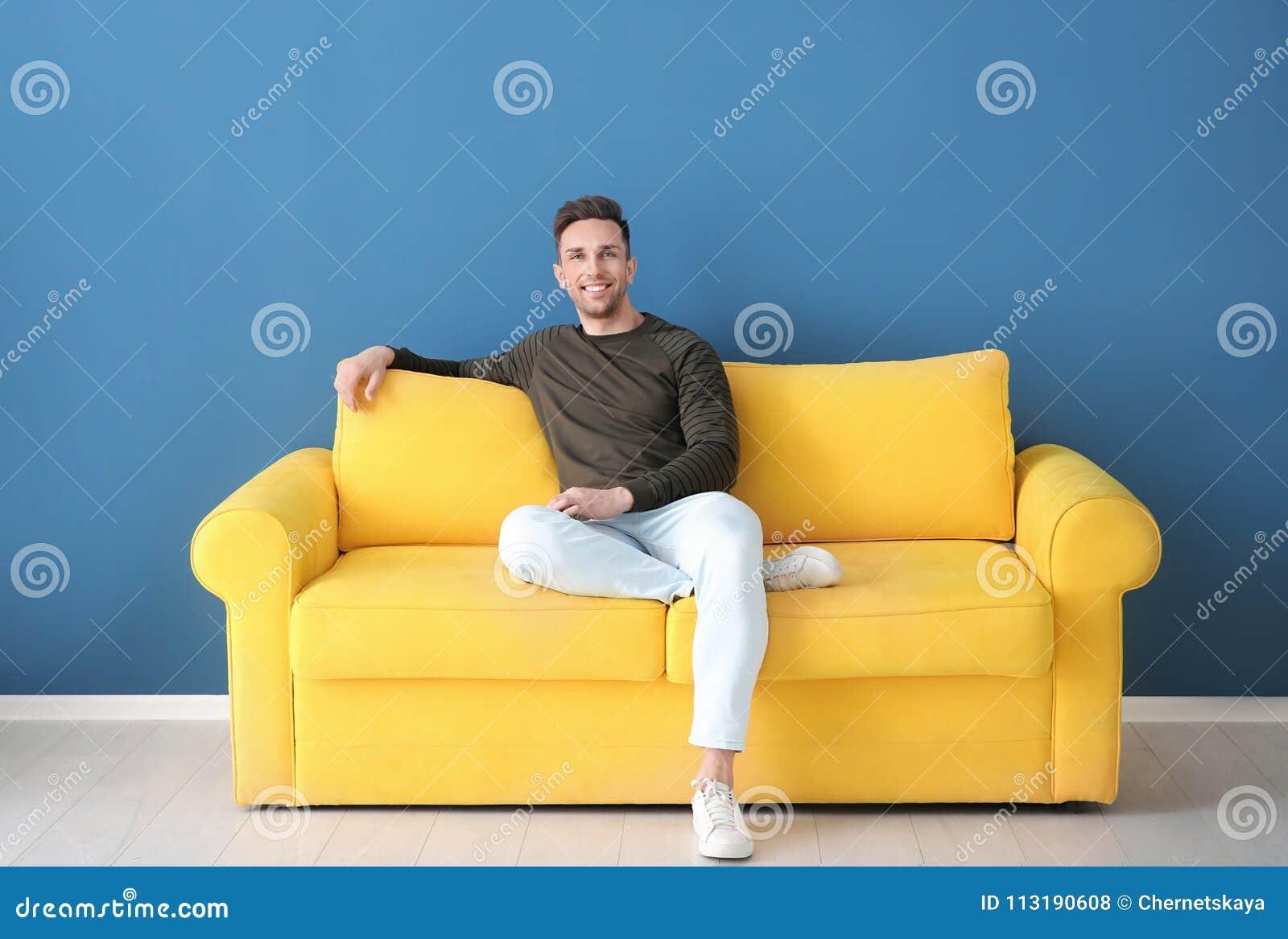 Stiligt sammanträde för ung man på soffan,