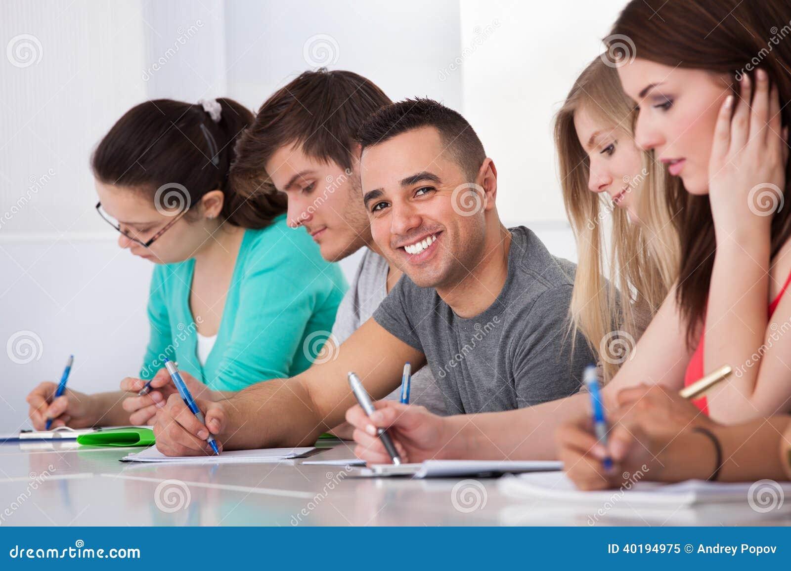 Stiligt studentsammanträde med klasskompisar som skriver på skrivbordet