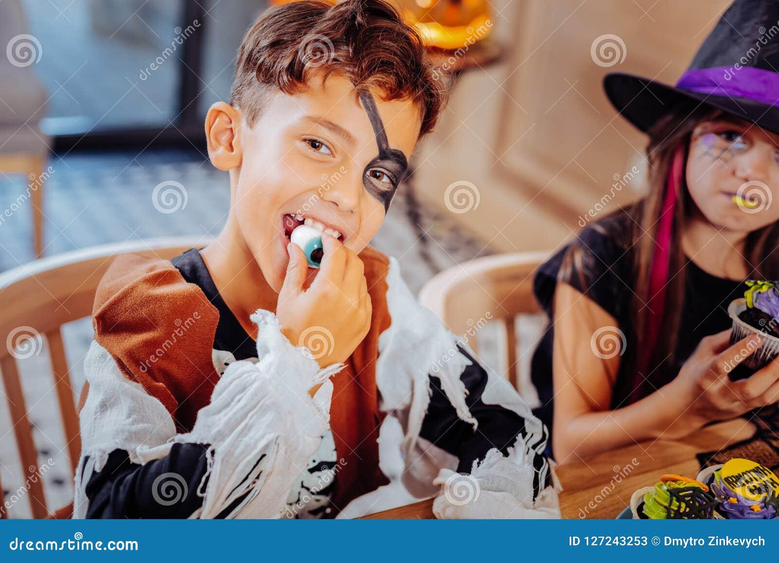 Stiligt svartögt bära för pojke piratkopierar dräkten för allhelgonaaftonen som äter det klibbiga ögat
