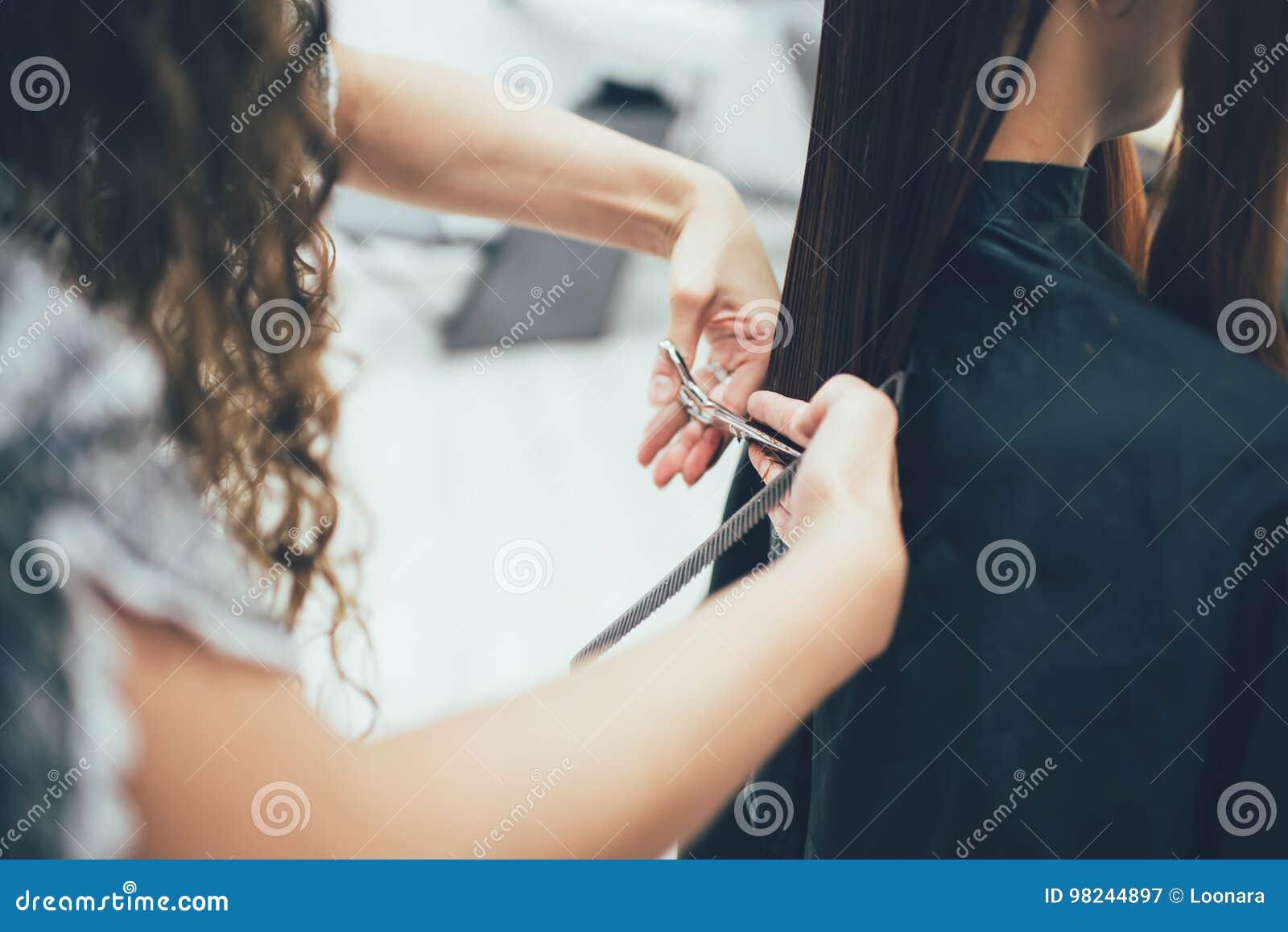 Stilist die in de schoonheidssalon, het kapsel en haar het stileren werken