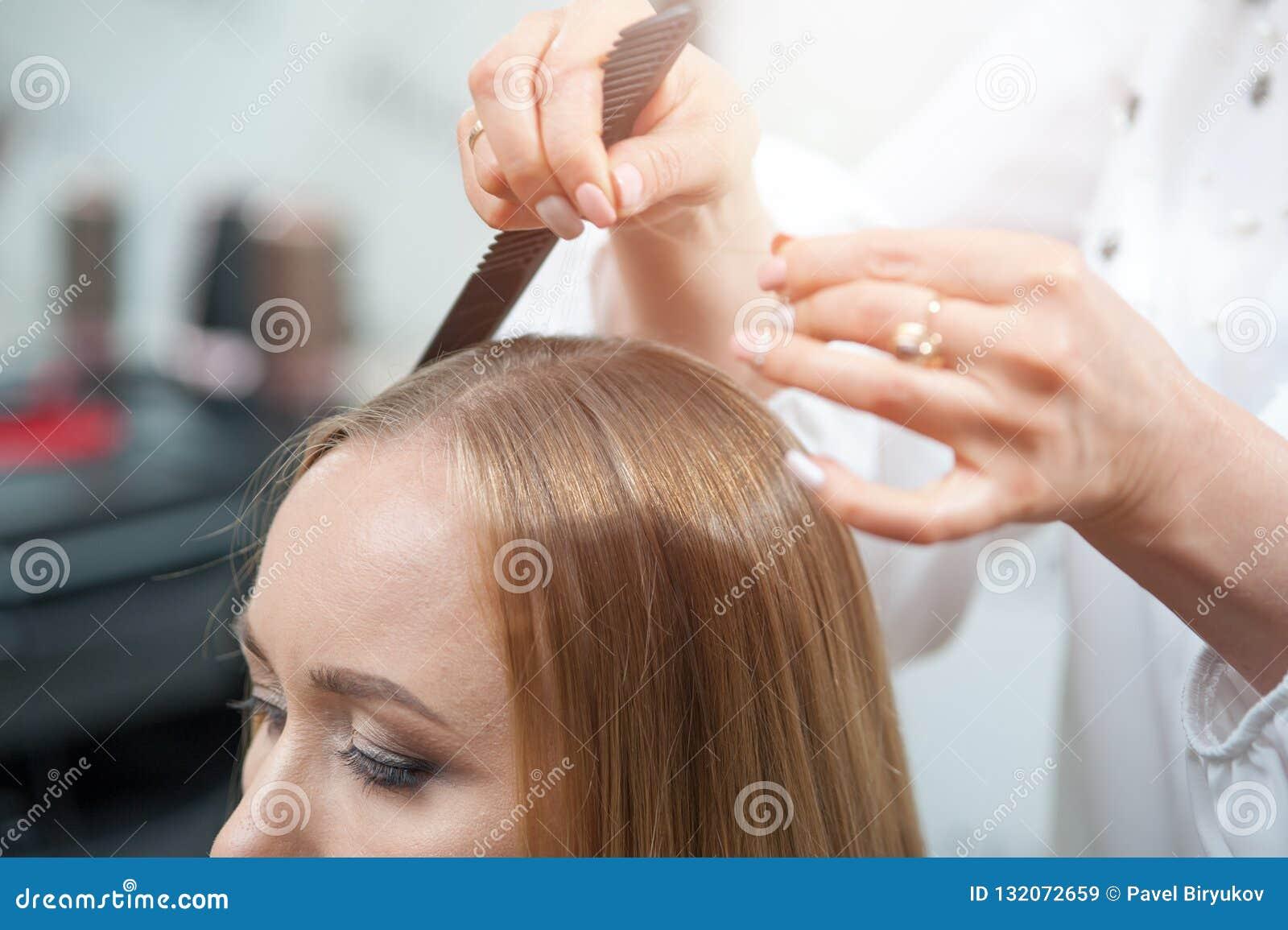 Stilist die het hairparting voor een vrouwelijke bezoeker van schoonheidssalon doen