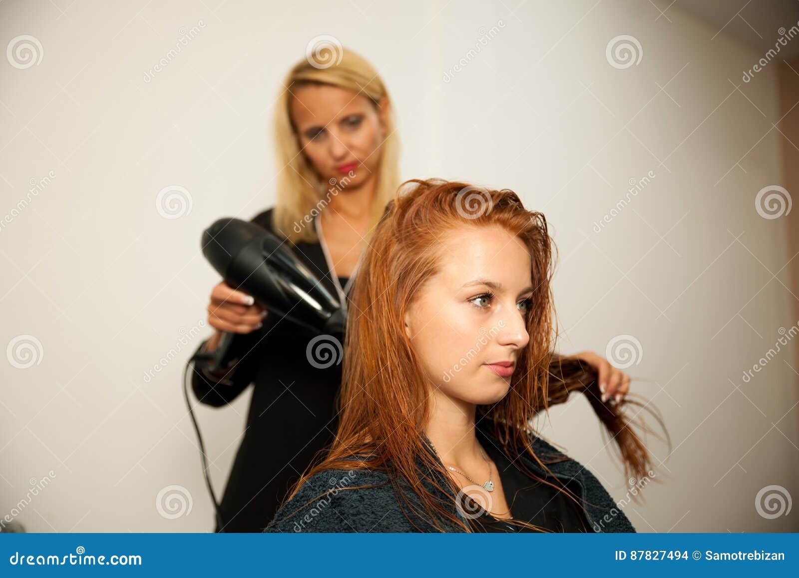 Stilist drogend haar van een vrouwelijke cliënt bij de schoonheidssalon - hai