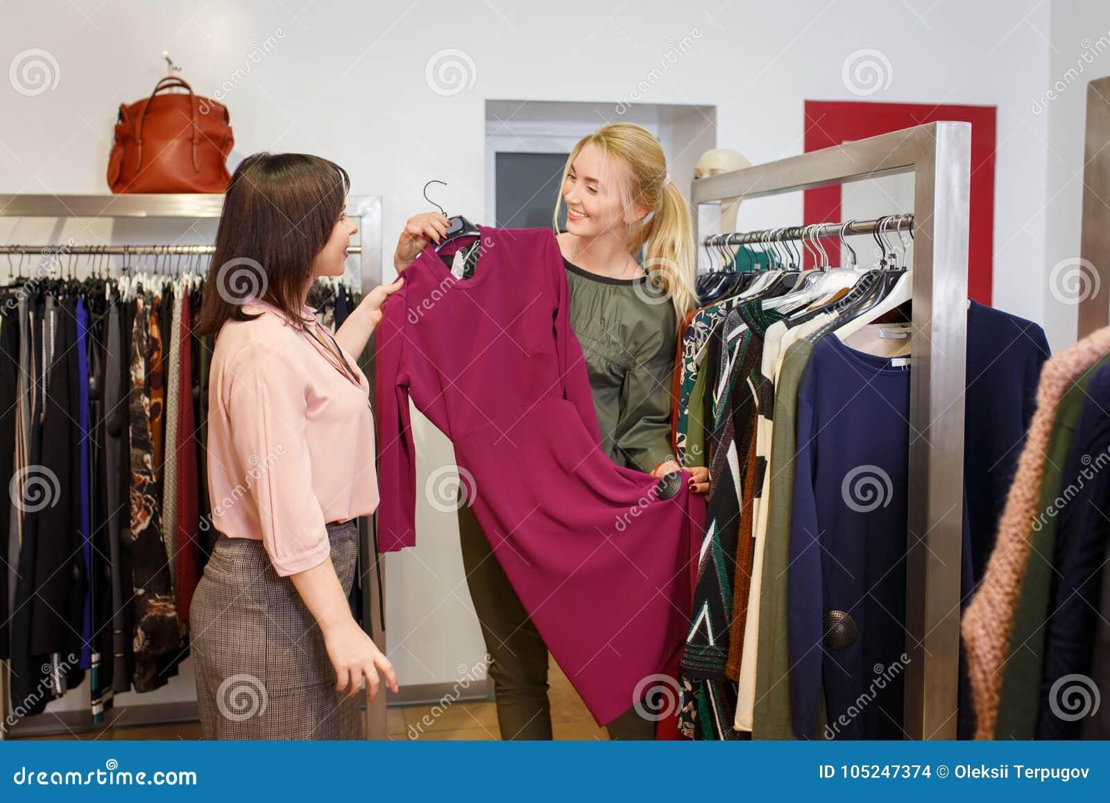Stilist het helpen kiest kleding voor de klant