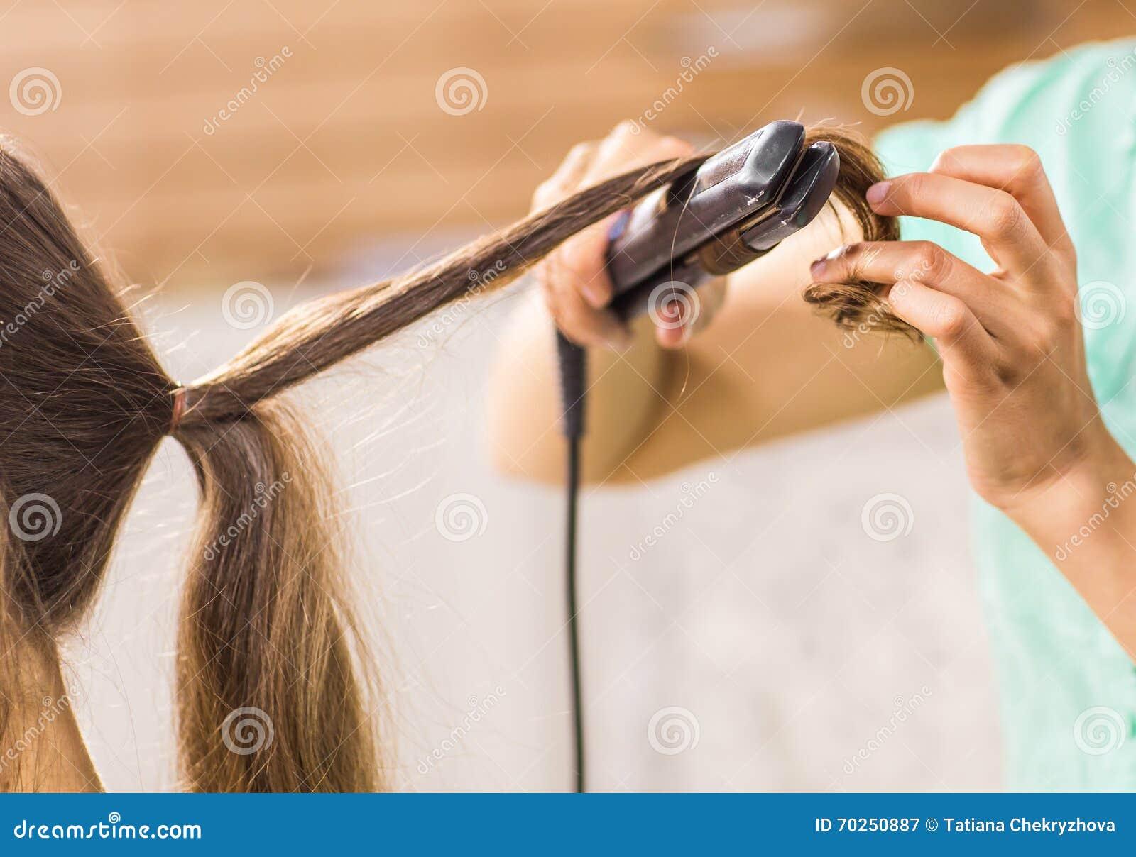 Stilist krullend haar voor jonge vrouw Meisjeszorg over haar kapsel