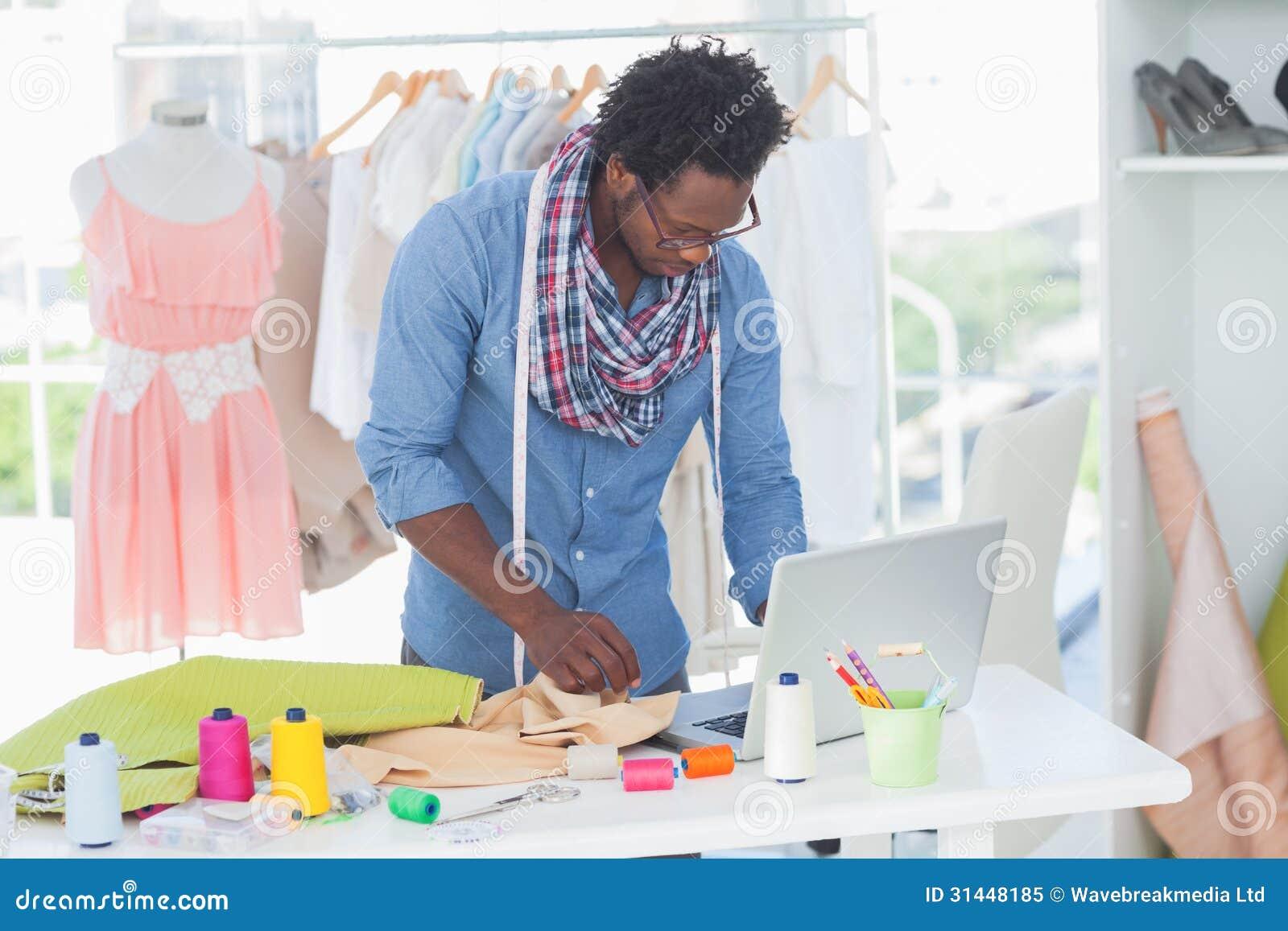 Stilista attraente che lavora al computer portatile