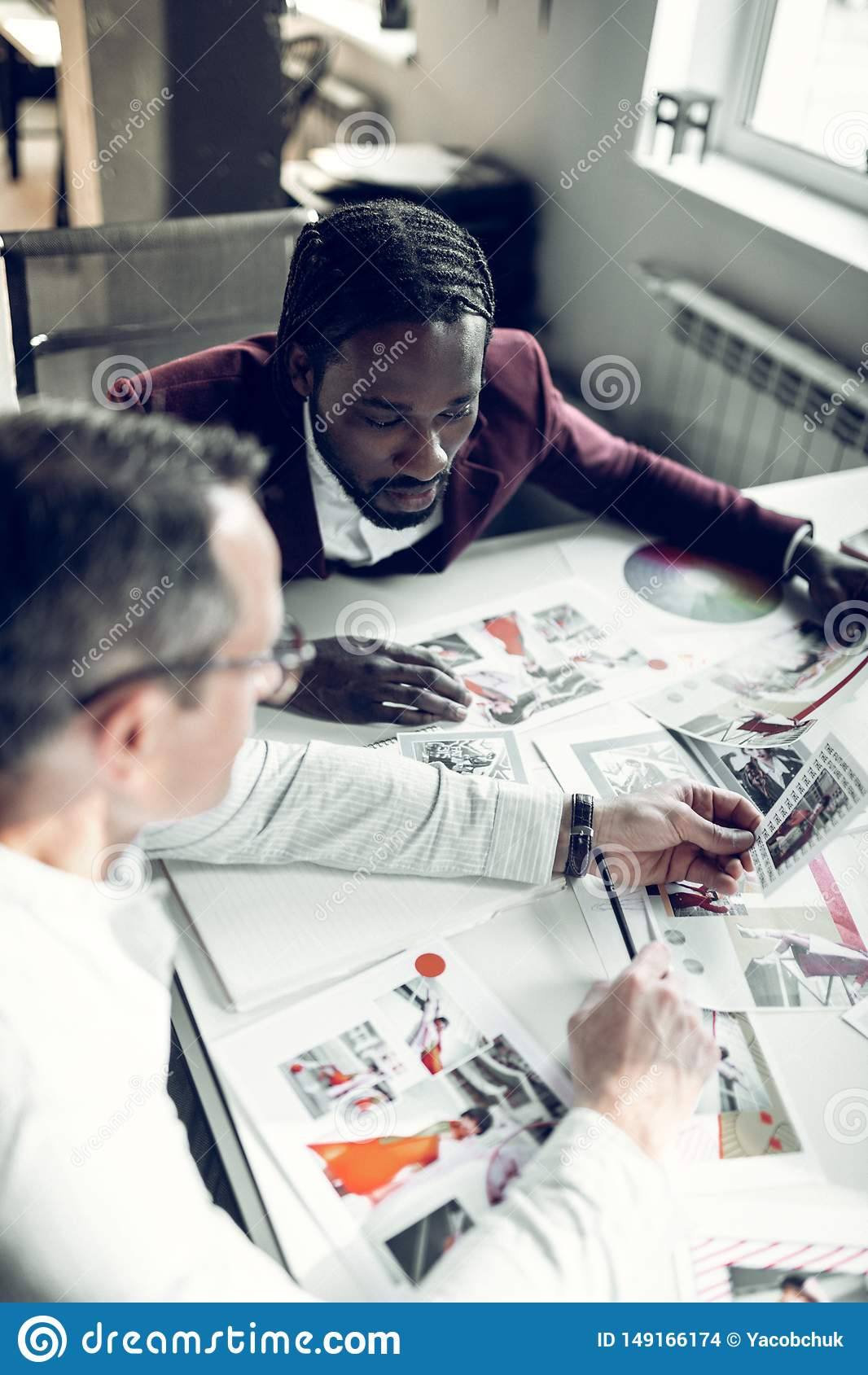 Stilisti maschii che esaminano le foto dei modelli