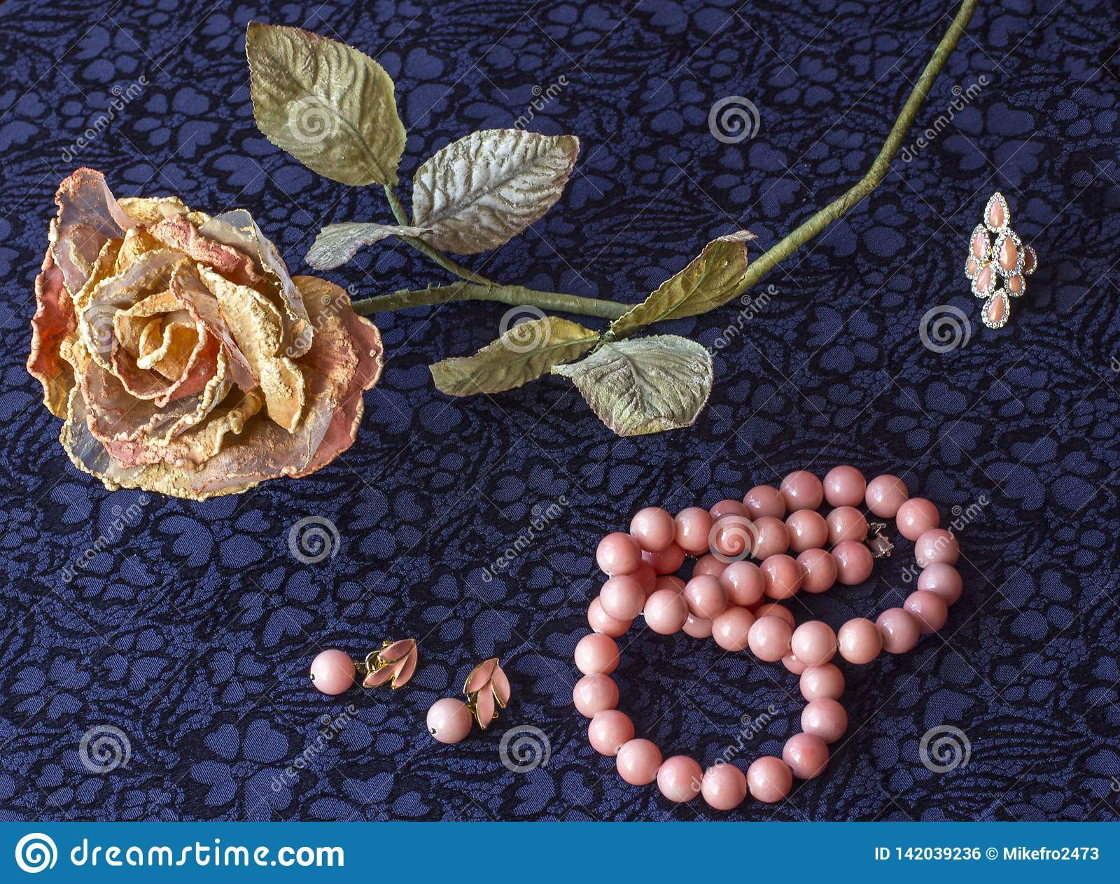 Still life of artificial rose with rose beads, earrings, brooch on textile background