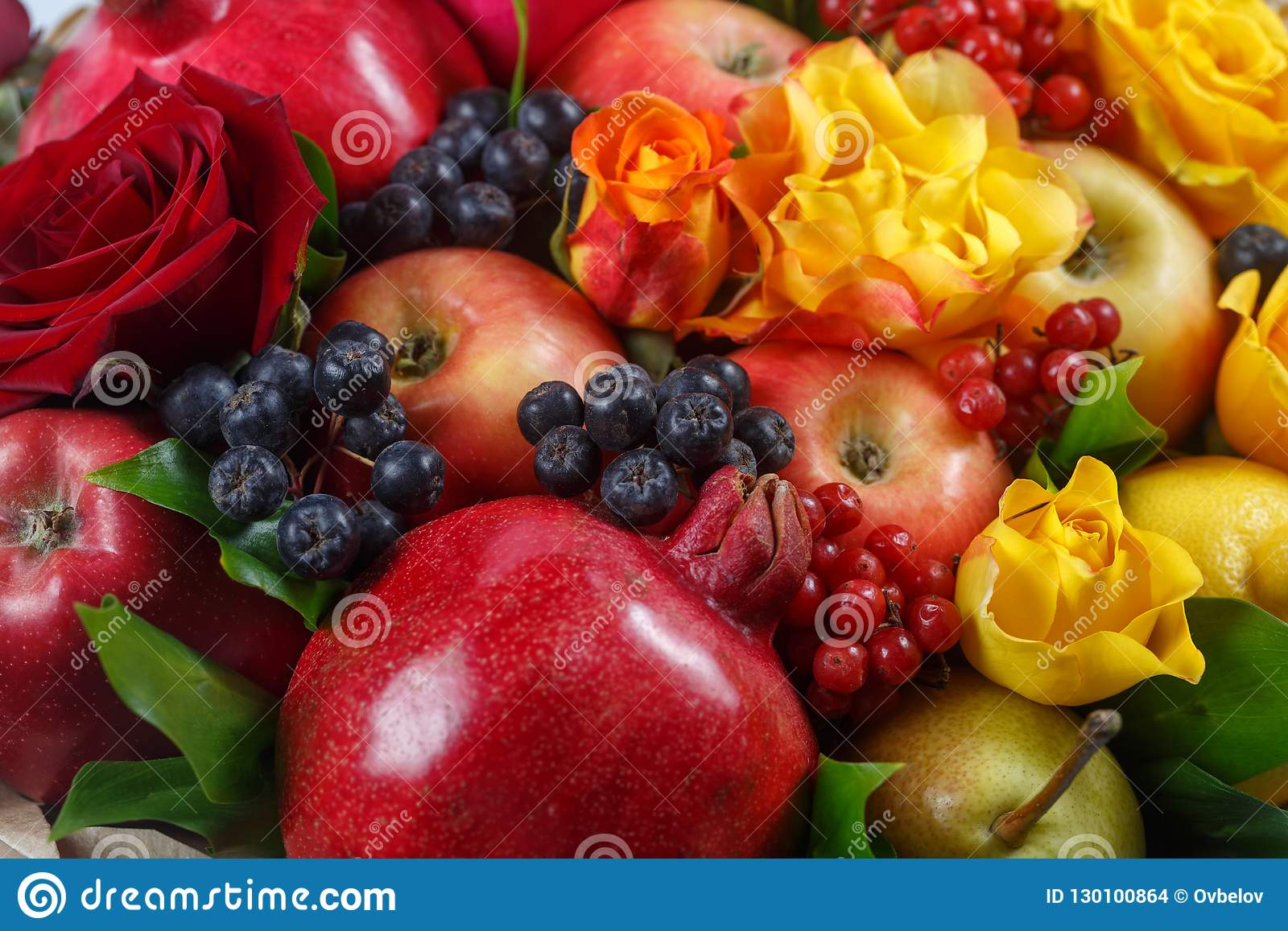 Still life consisting of pomegranates, apples, black rowan, red viburnum, pears, lemons and flowers of red and yellow roses close-