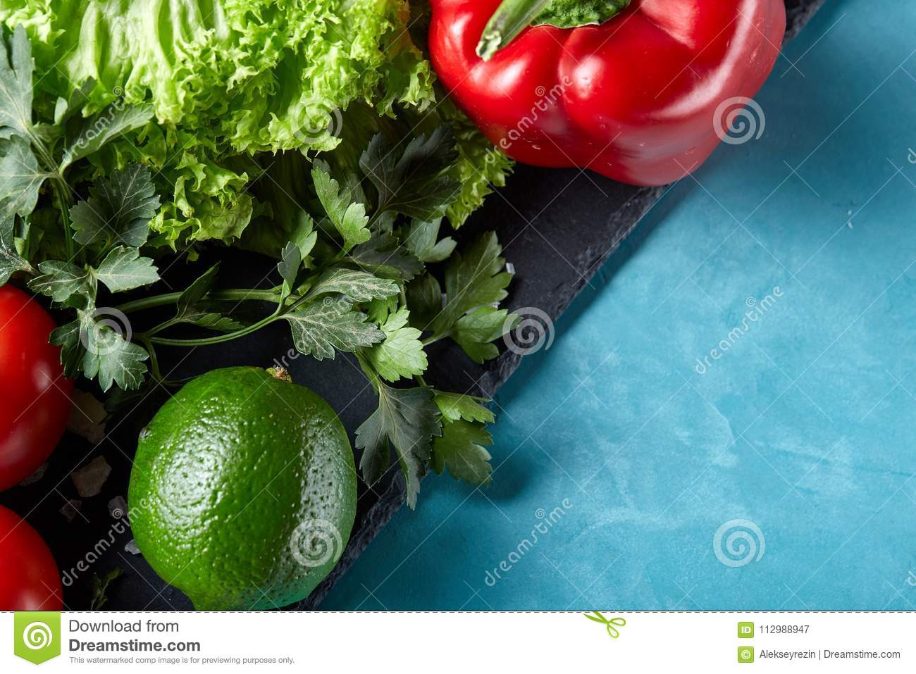 Still life of fresh organic vegetables on wooden plate over blue background, selective focus, close-up
