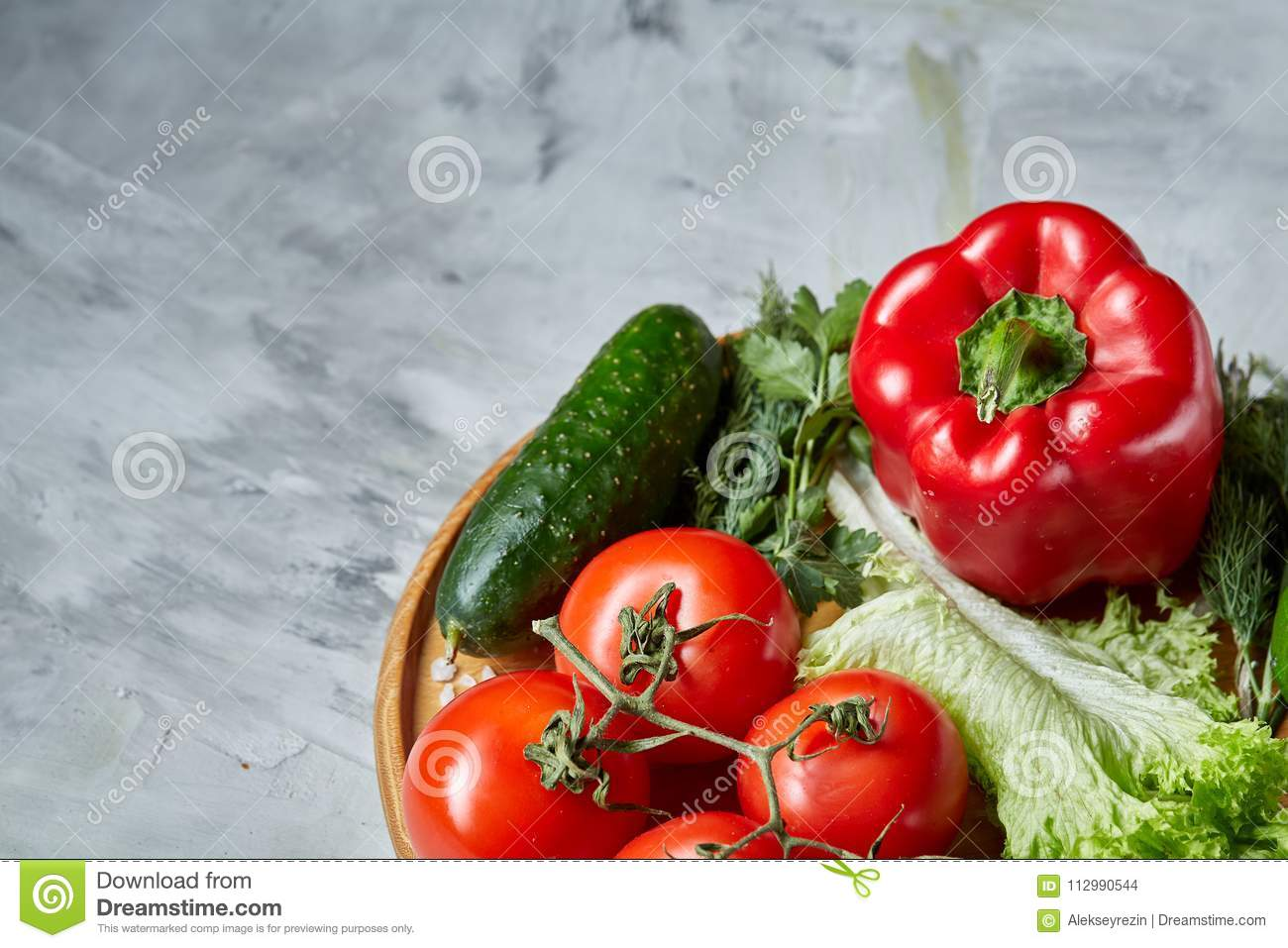 Still life of fresh organic vegetables on wooden plate over white background, selective focus, close-up